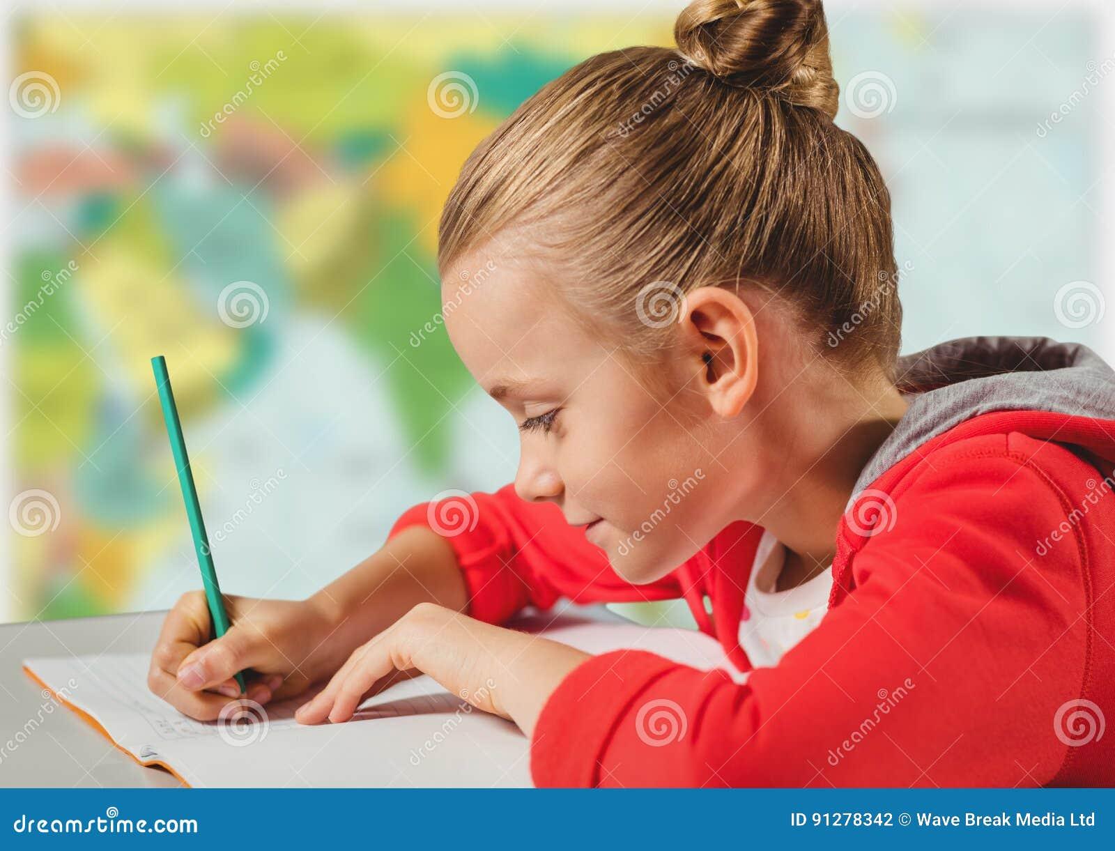 Flicka som gör läxa mot oskarp översikt