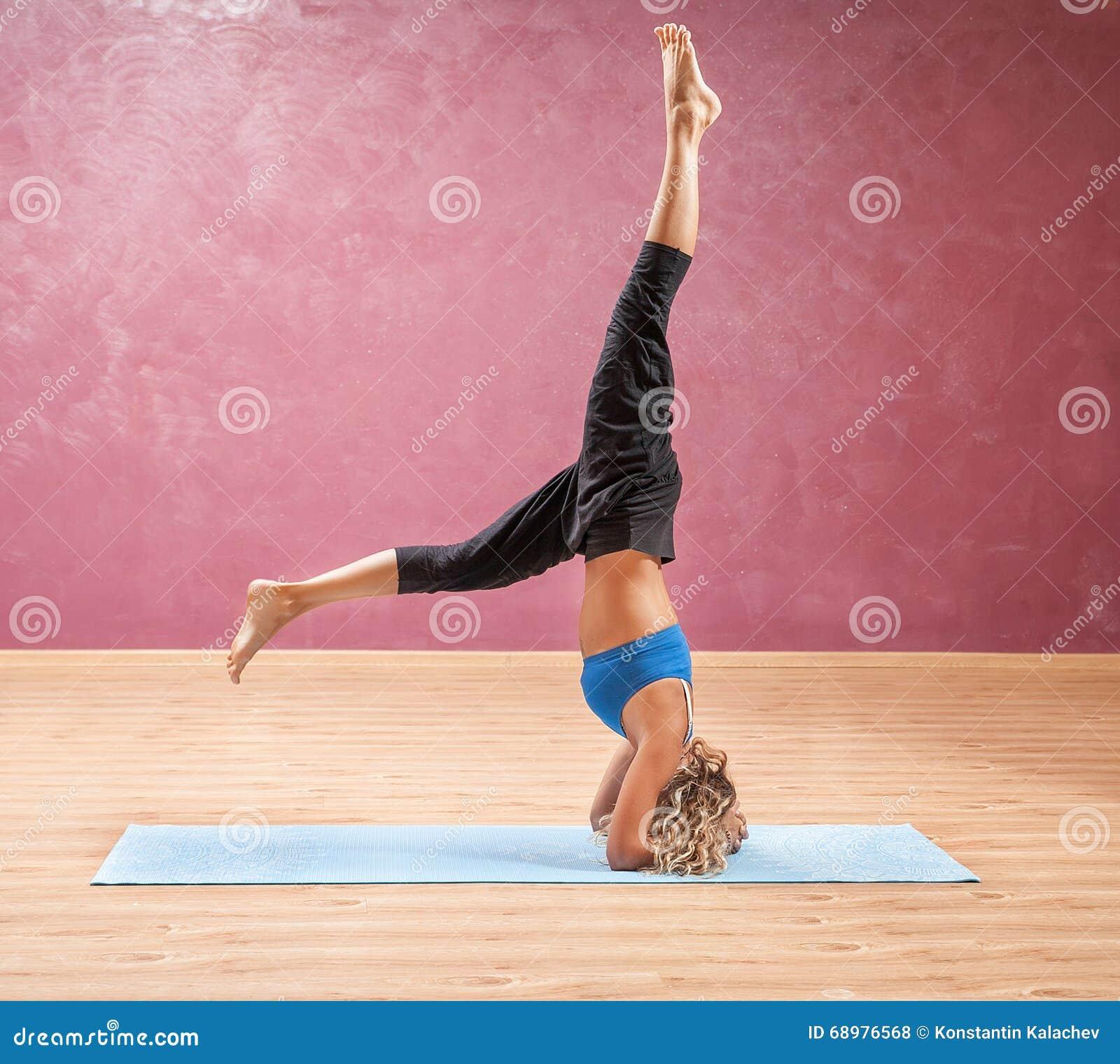 Flicka som gör yogaanseende på head uppochnervänt