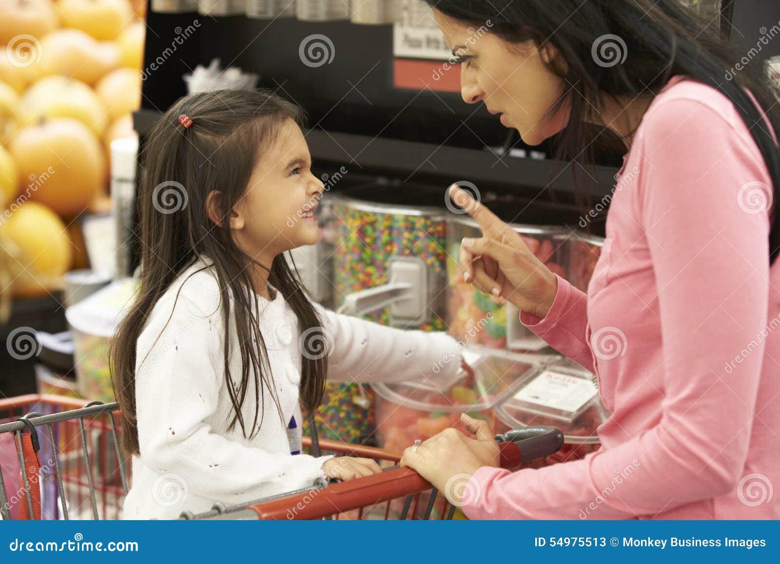 Flicka som har argument med modern på godisräknaren i supermarket