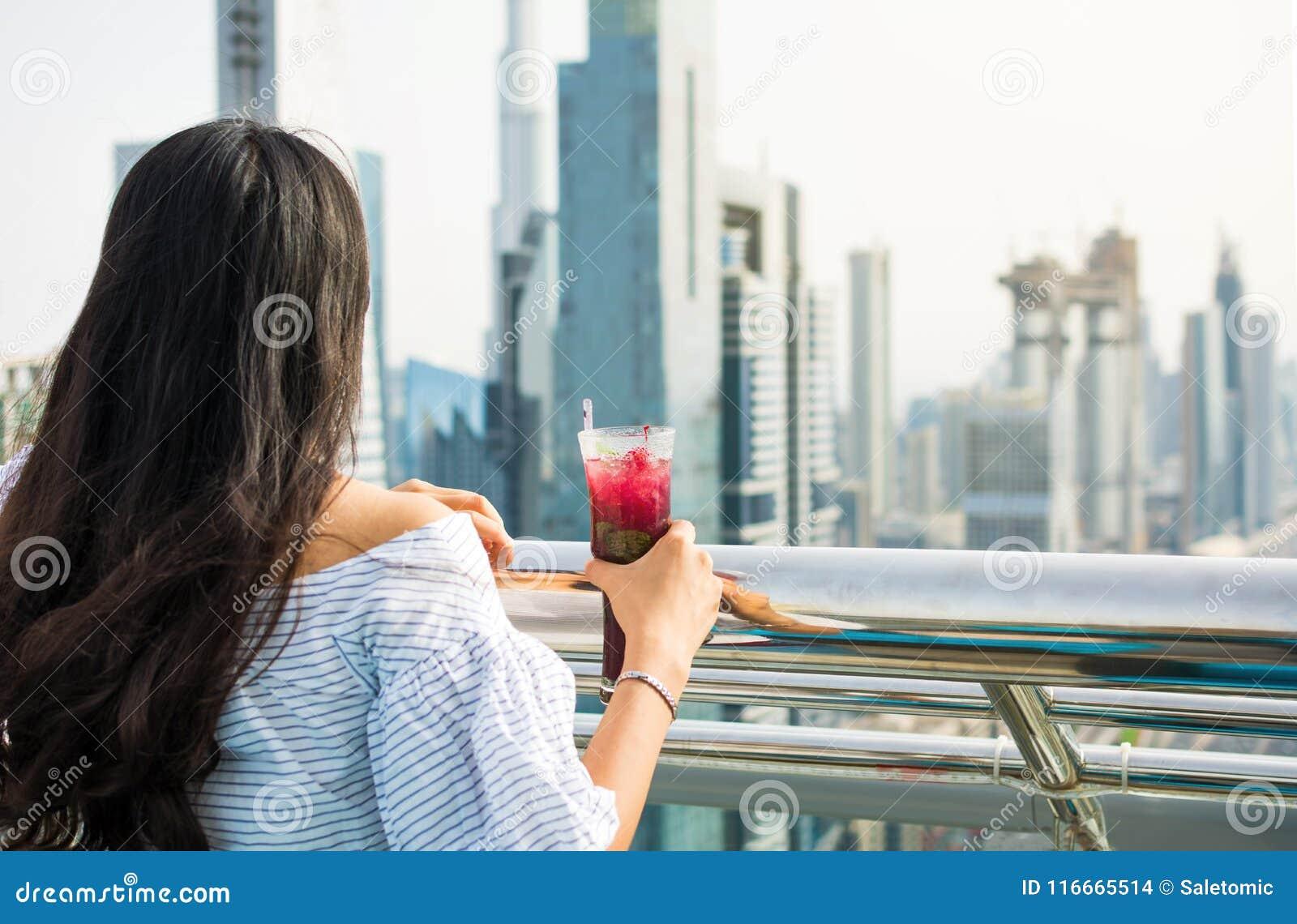 Flicka som har en drink med den Dubai sikten