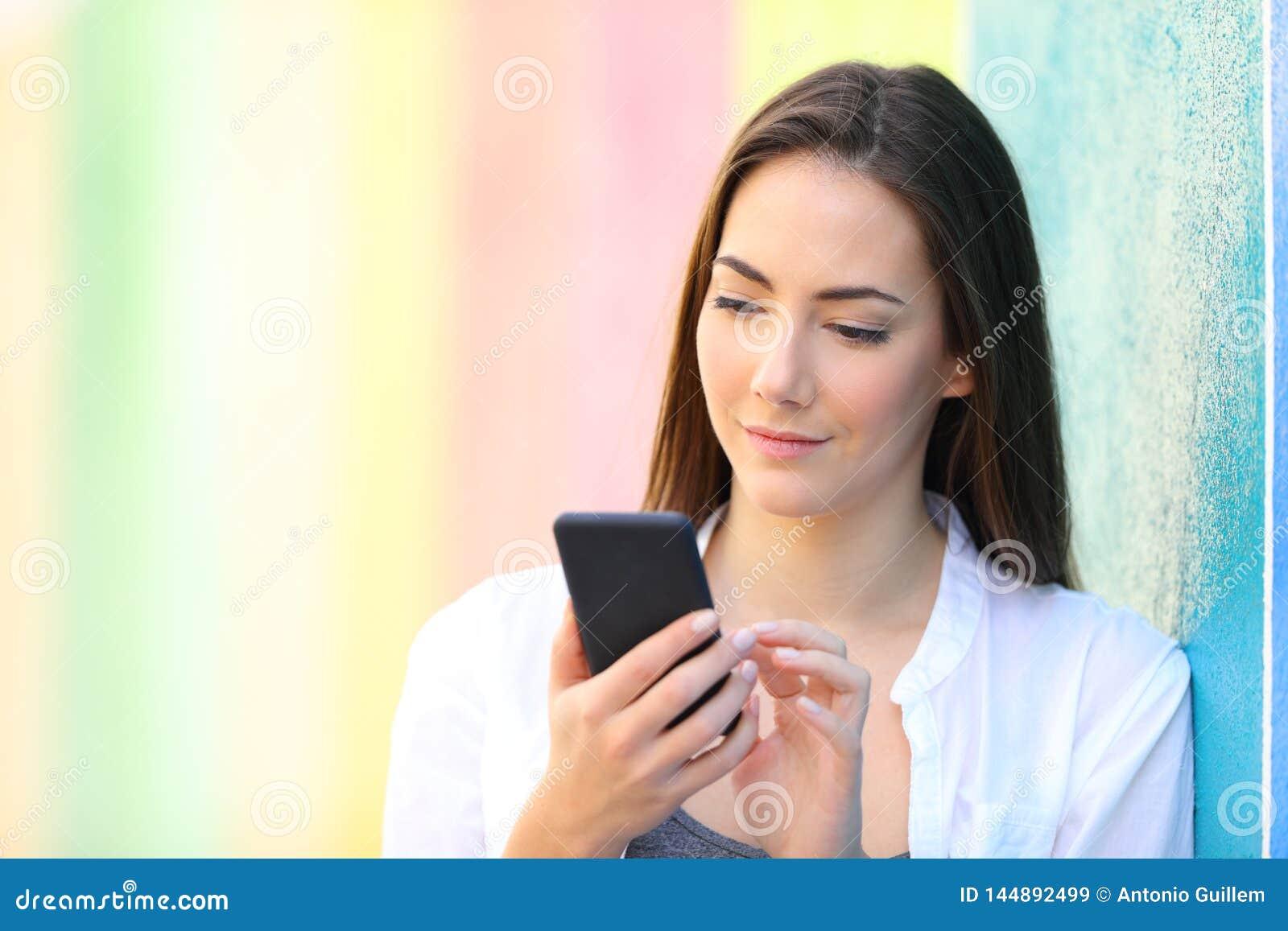 Flicka som kontrollerar den smarta telefonen i en färgrik gata