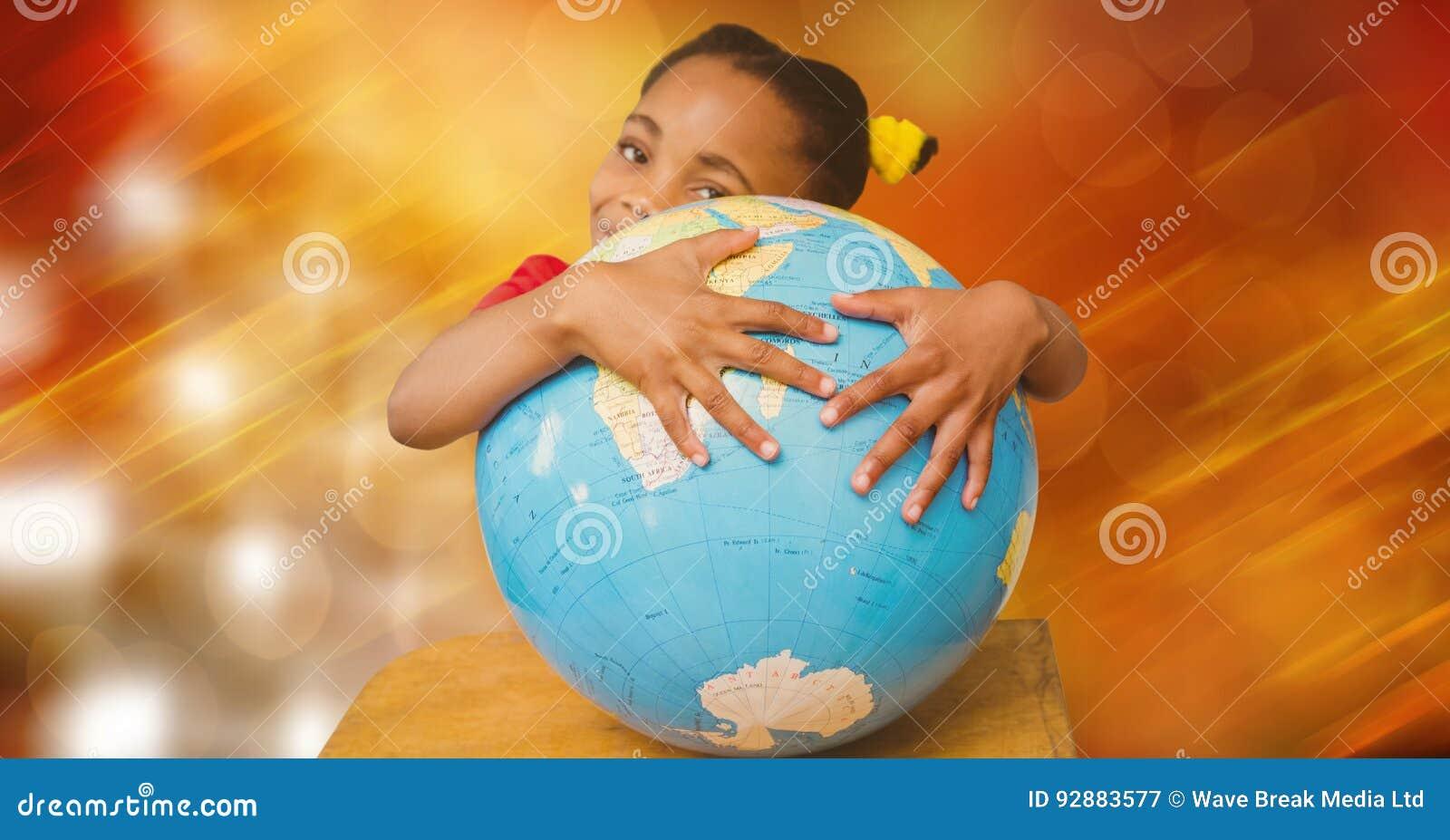 Flicka som kramar jordklotet mot suddighetsbakgrund