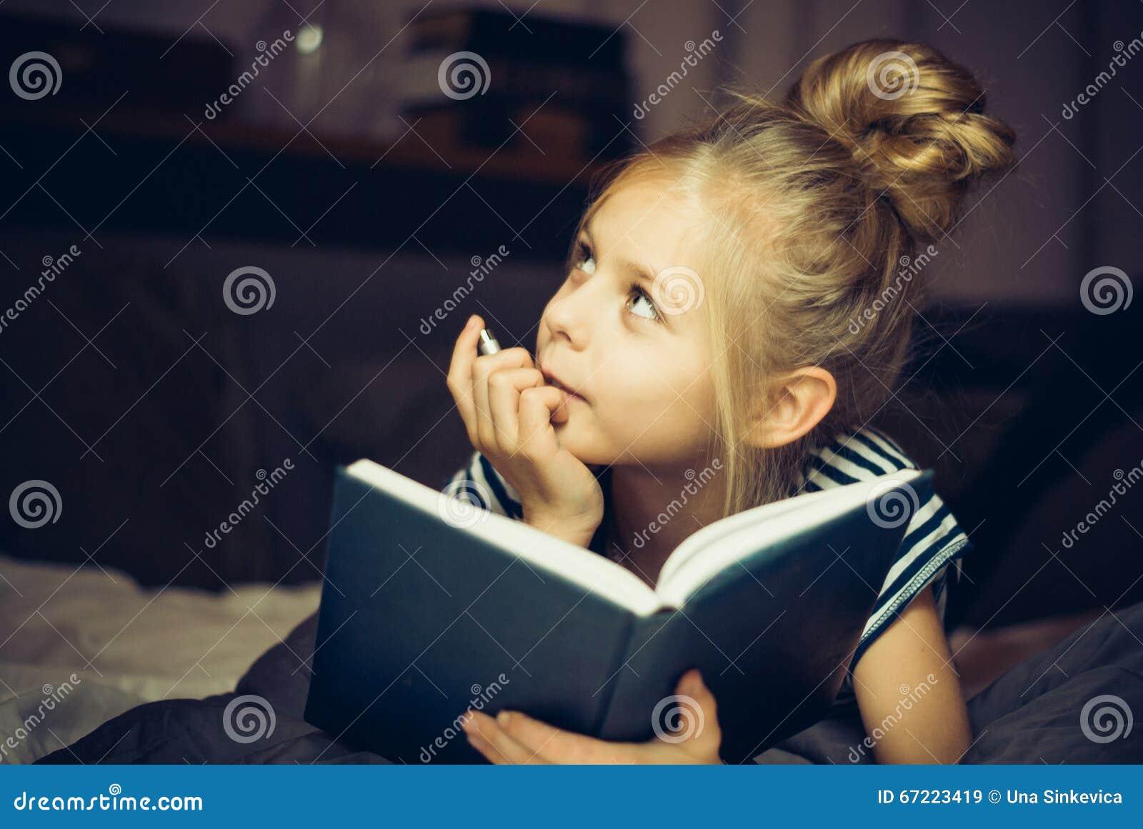 Flicka som läser en bok och drömmar i säng