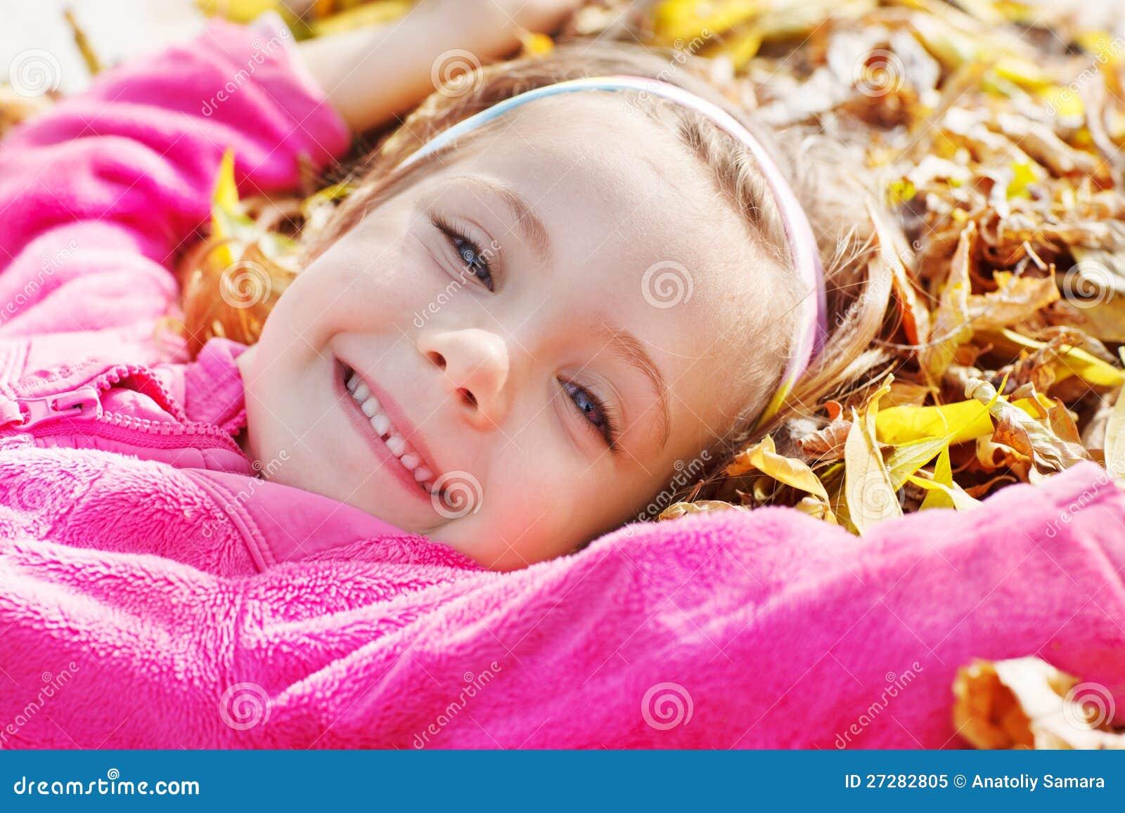 Flicka som ligger på gula leaves