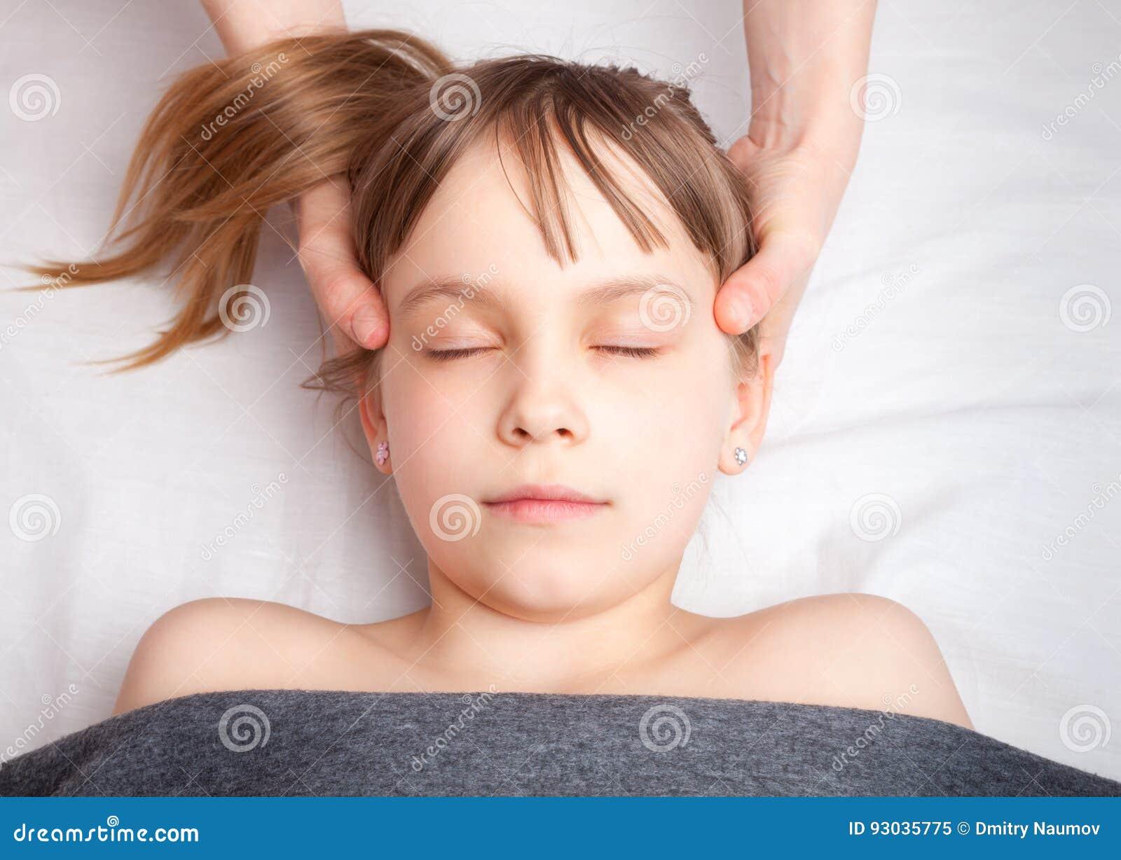 Flicka som mottar osteopathic behandling av hennes huvud