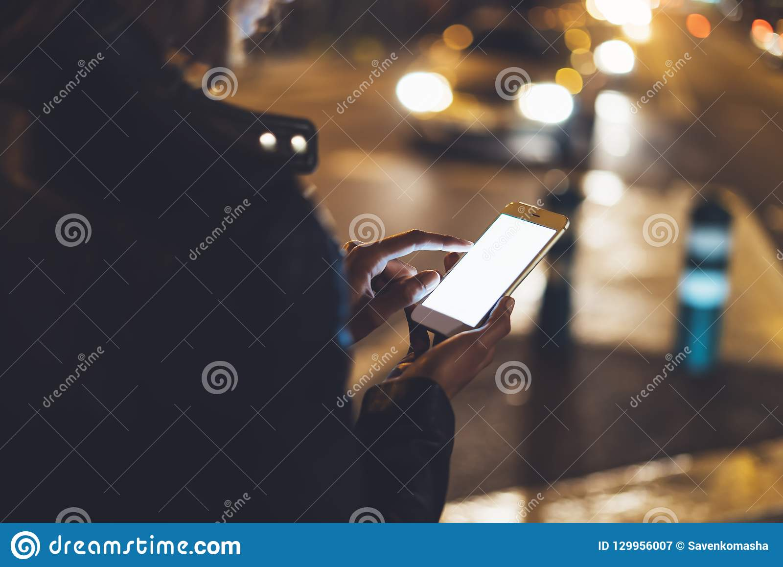 Flicka som pekar fingret på skärmsmartphonen på bakgrundsbokehljus i atmosfärisk stadsgata för natt, använda för bloggerhipsterfl
