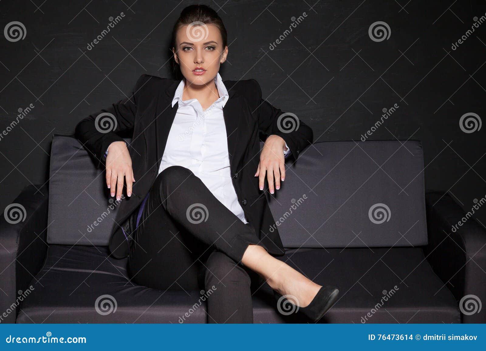 Flicka som poserar i studion på soffan