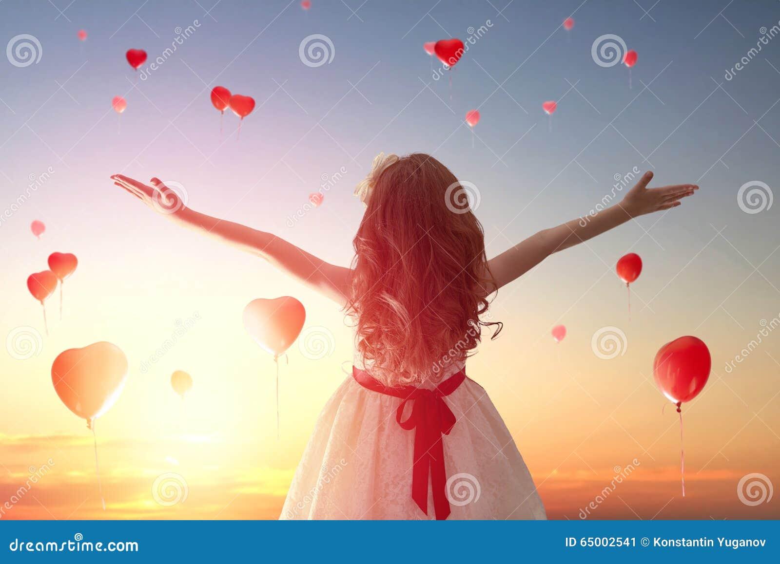 Flicka som ser röda ballonger