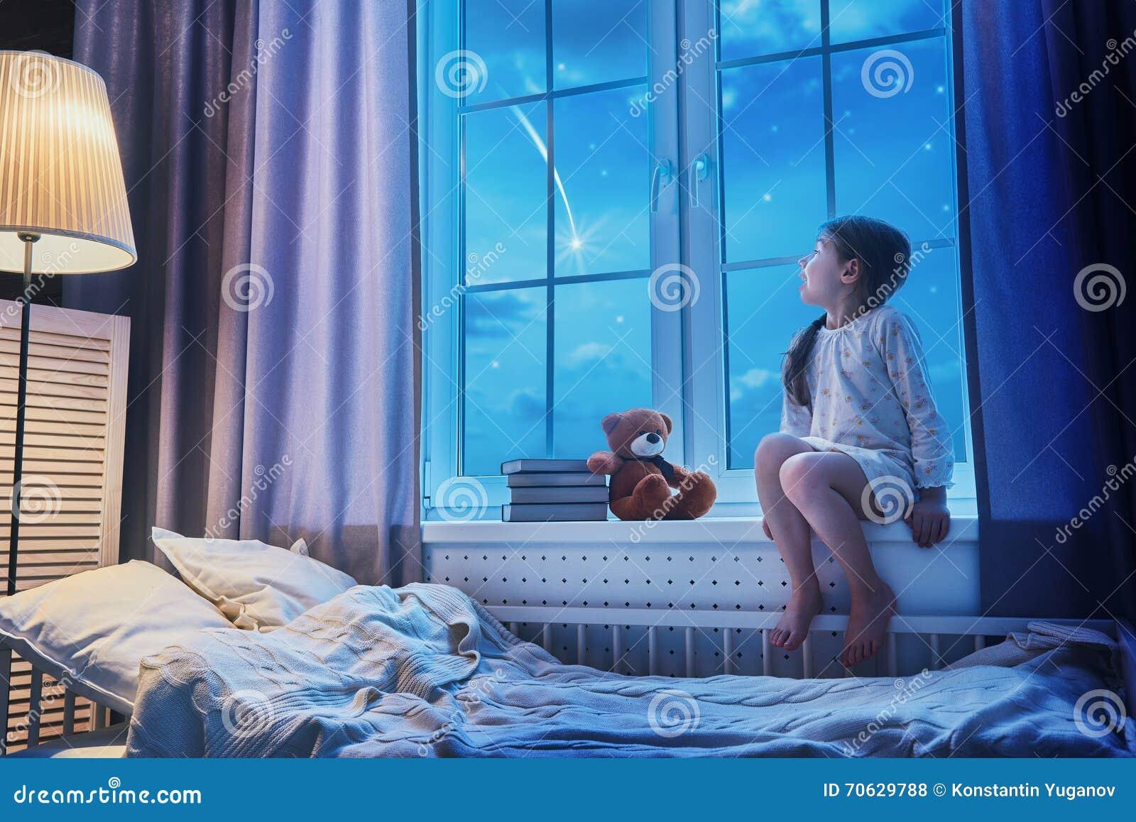Flicka som sitter på fönstret