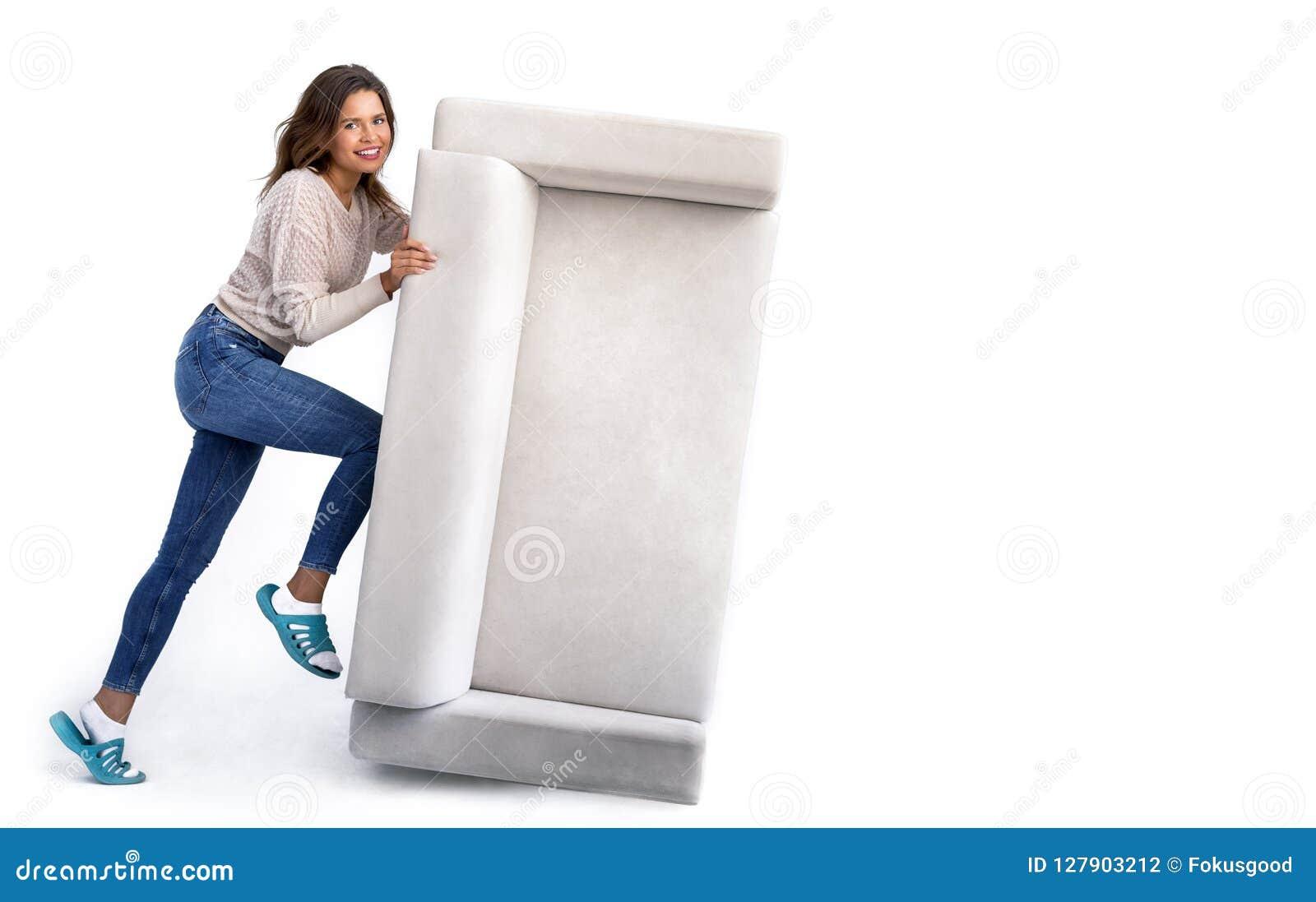 Flicka som skjuter en gammal soffa