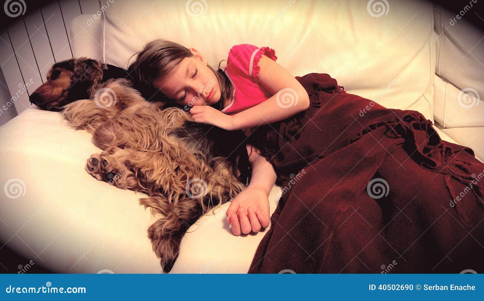 Flicka som sover med hennes älsklings- hund