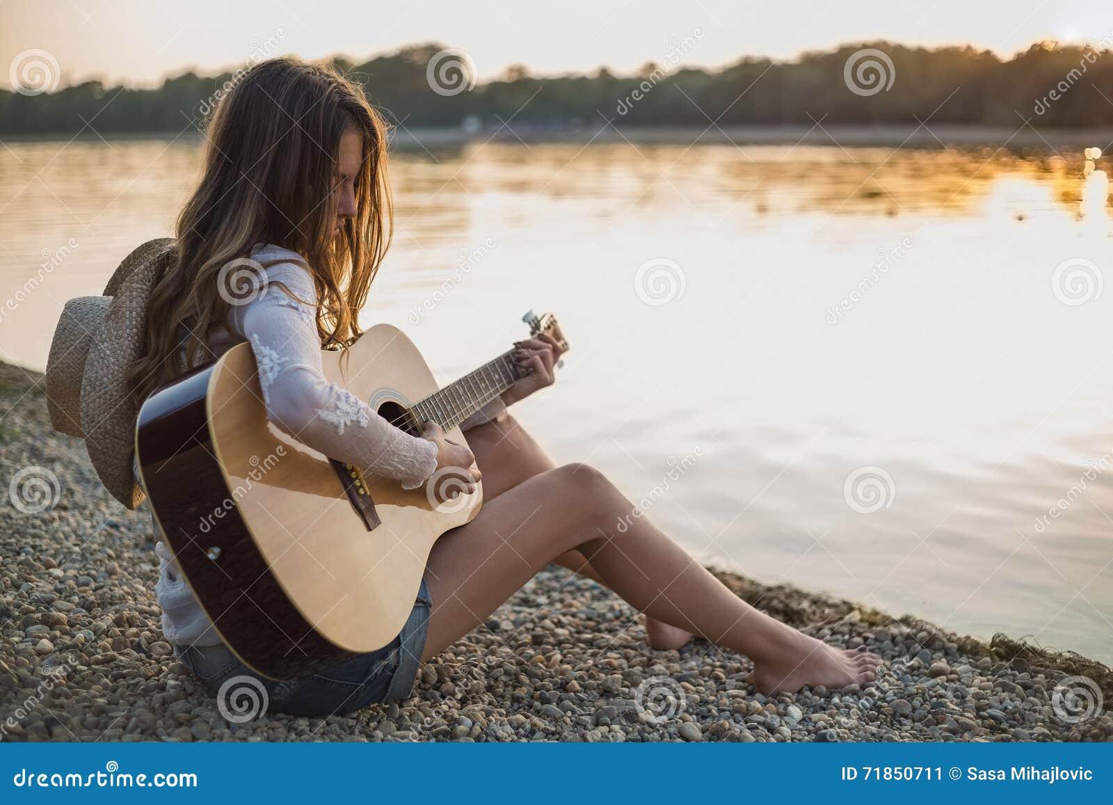 Flicka som spelar gitarren, medan sitta på stranden