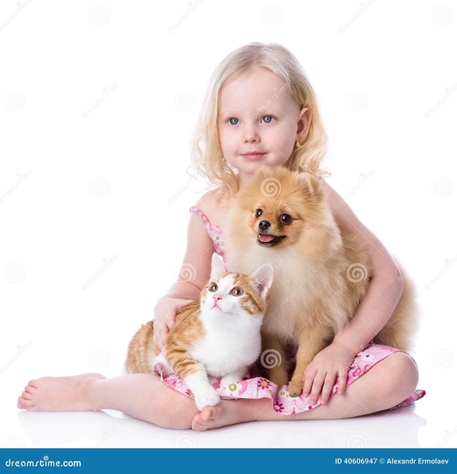 Flicka som spelar med husdjur - hund och katt