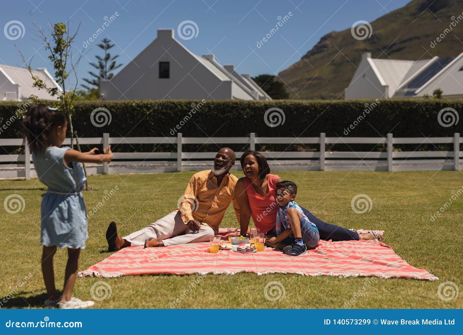 Flicka som tar bilder av denutveckling familjen med mobiltelefonen på trädgården