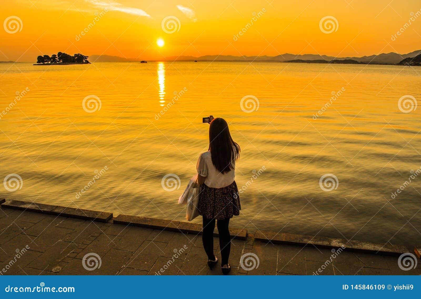 Flicka som tar en bild av solnedgången över en sjö