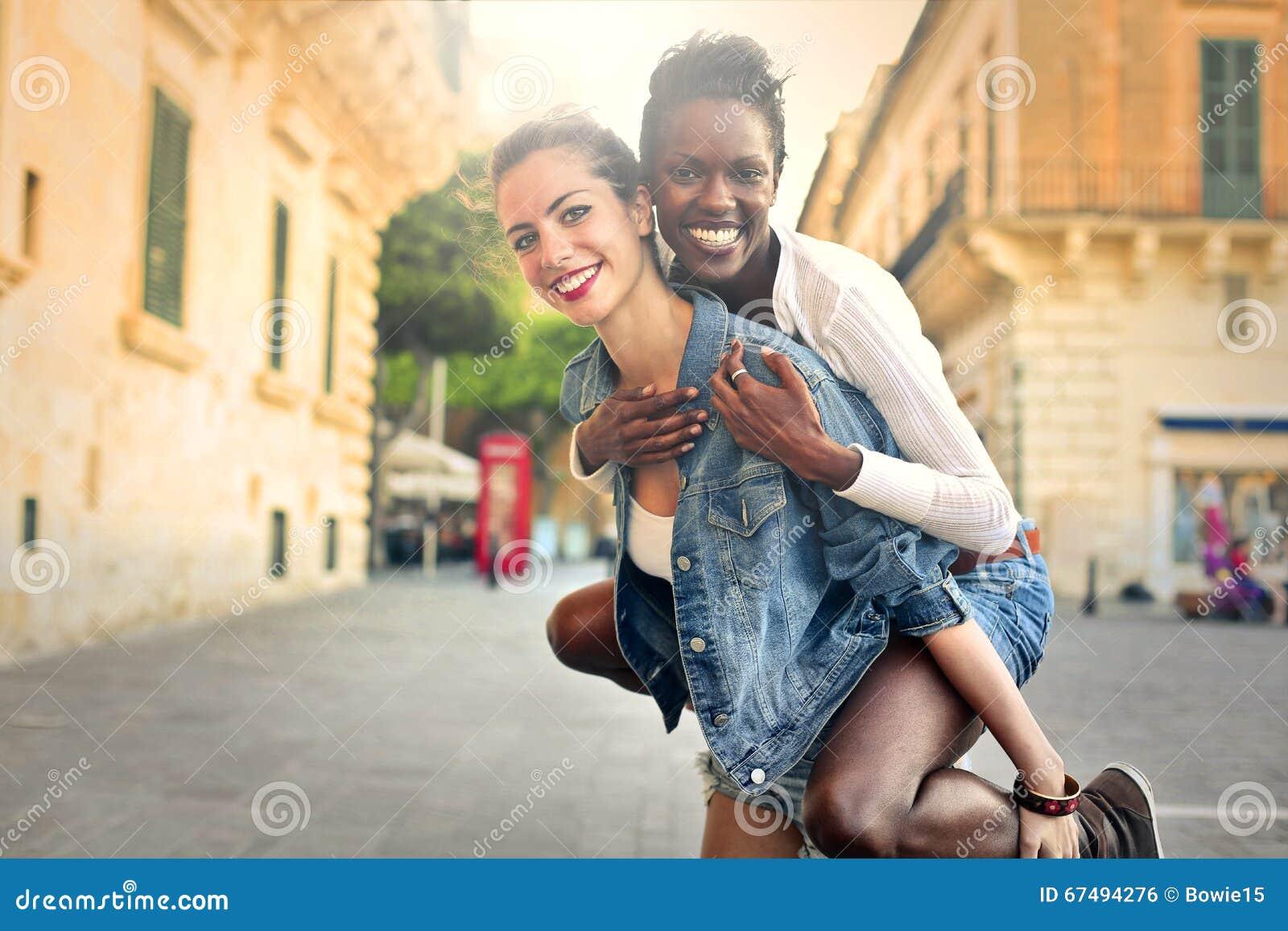 Flicka som tillbaka bär en vän på henne