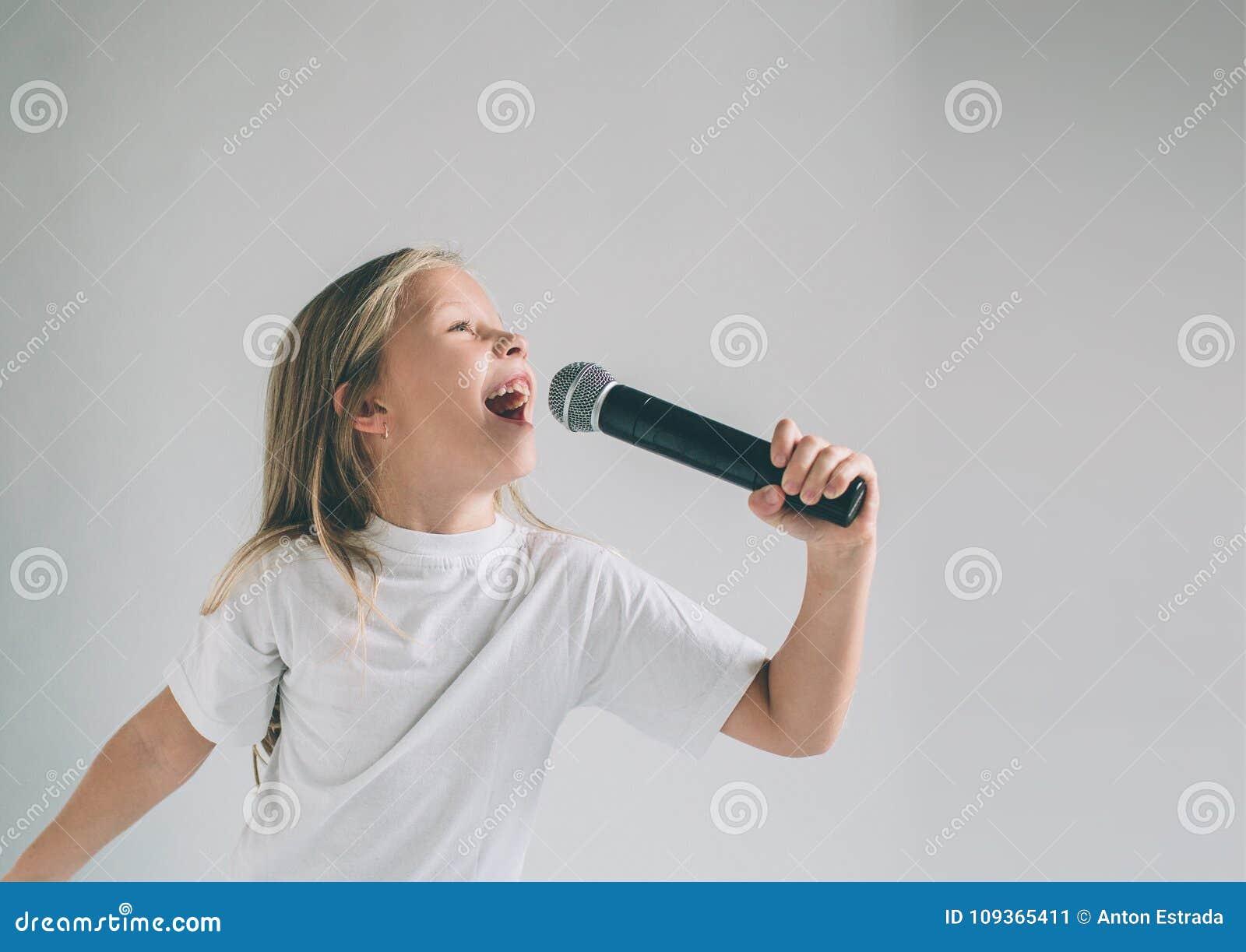Flicka som ut vaggar Bild av ett barn som sjunger till mikrofonen som isoleras på ljus Emotionell stående av en attraktiv unge