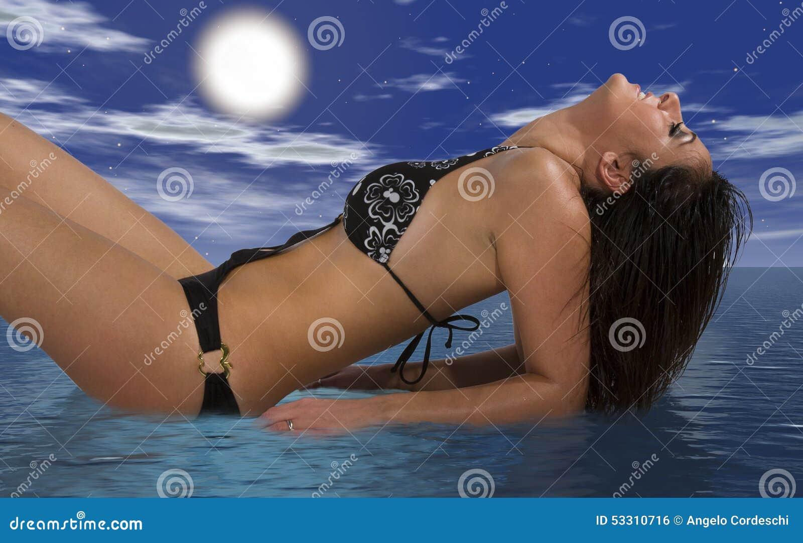 Flickabaddräkt som kopplar av att ligga på havet, head vippad på baksida clouds skyen