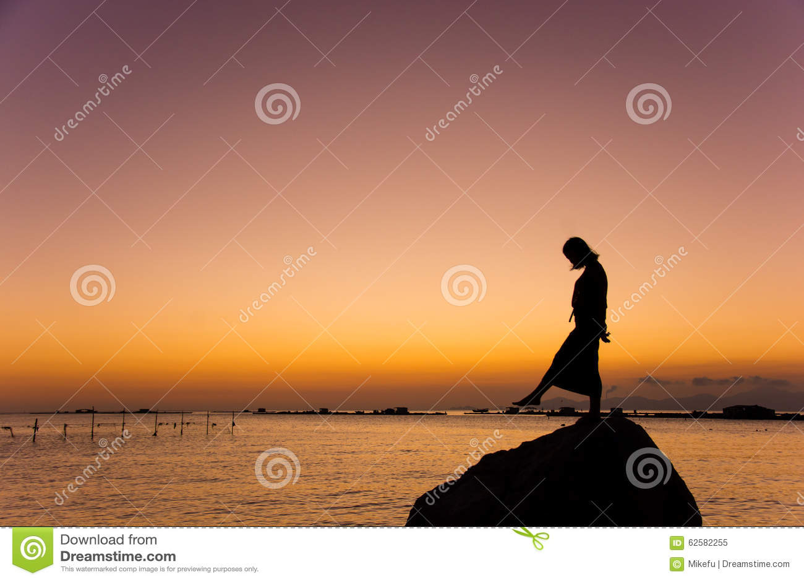 Flickadans på stranden på solnedgången
