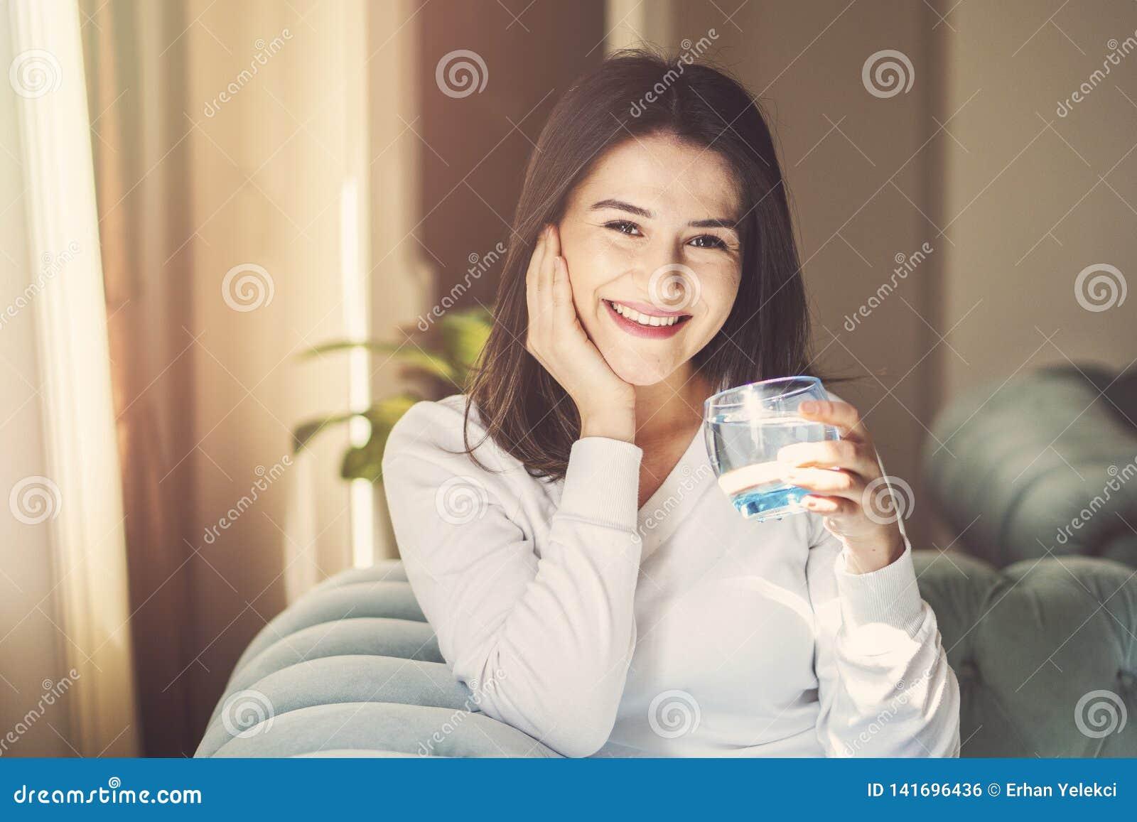 Flickadricksvatten som hemma sitter på en soffa