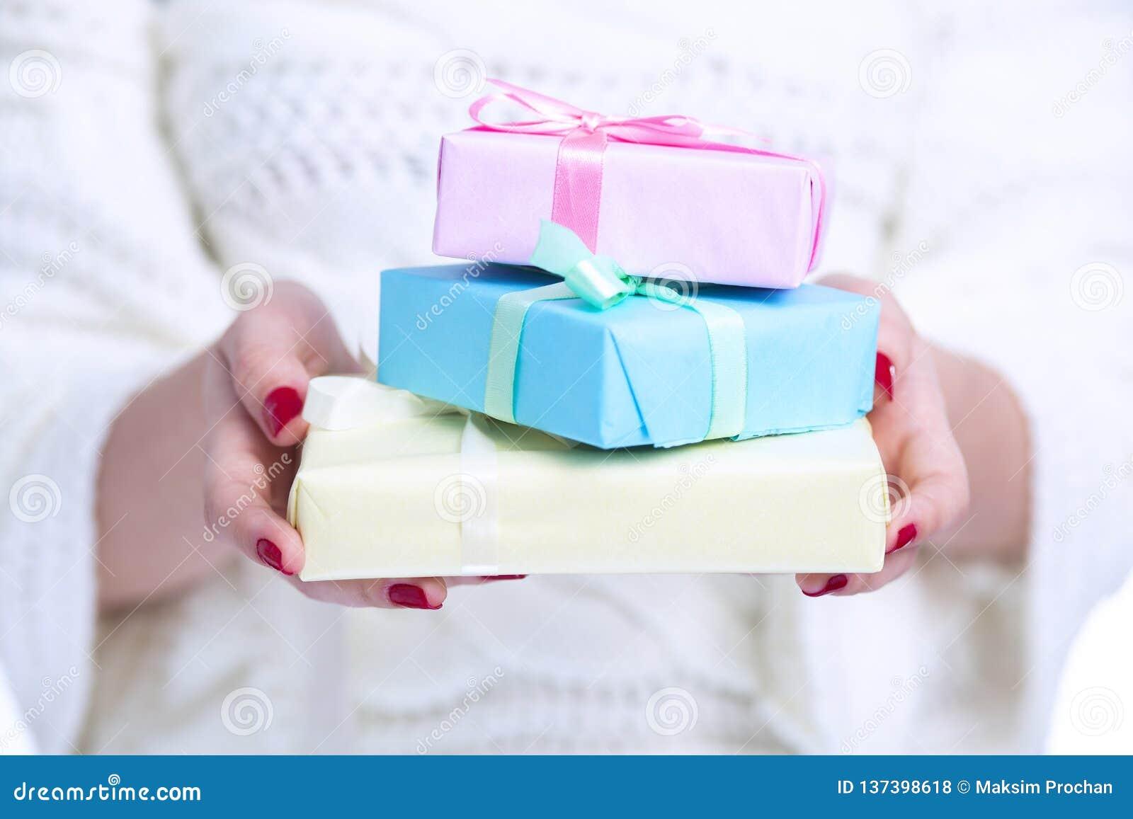 Flickainnehavhög av gåvaaskar i händer, kvinna med gåvor som slås in i kulört dekorativt papper på vit isolerad bakgrund,