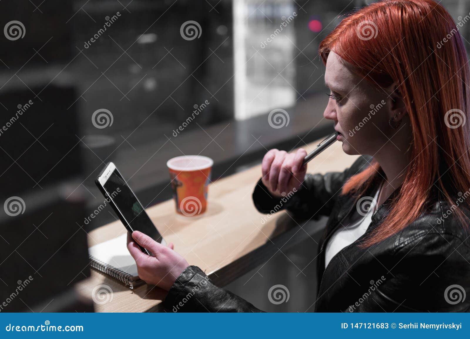 Flickainnehavsmartphonen i hand, sitter i kaf?t, arbete, pennan, bruksgrej N?tverk wifi, samkv?m, kommunikation Freelancerarbeten
