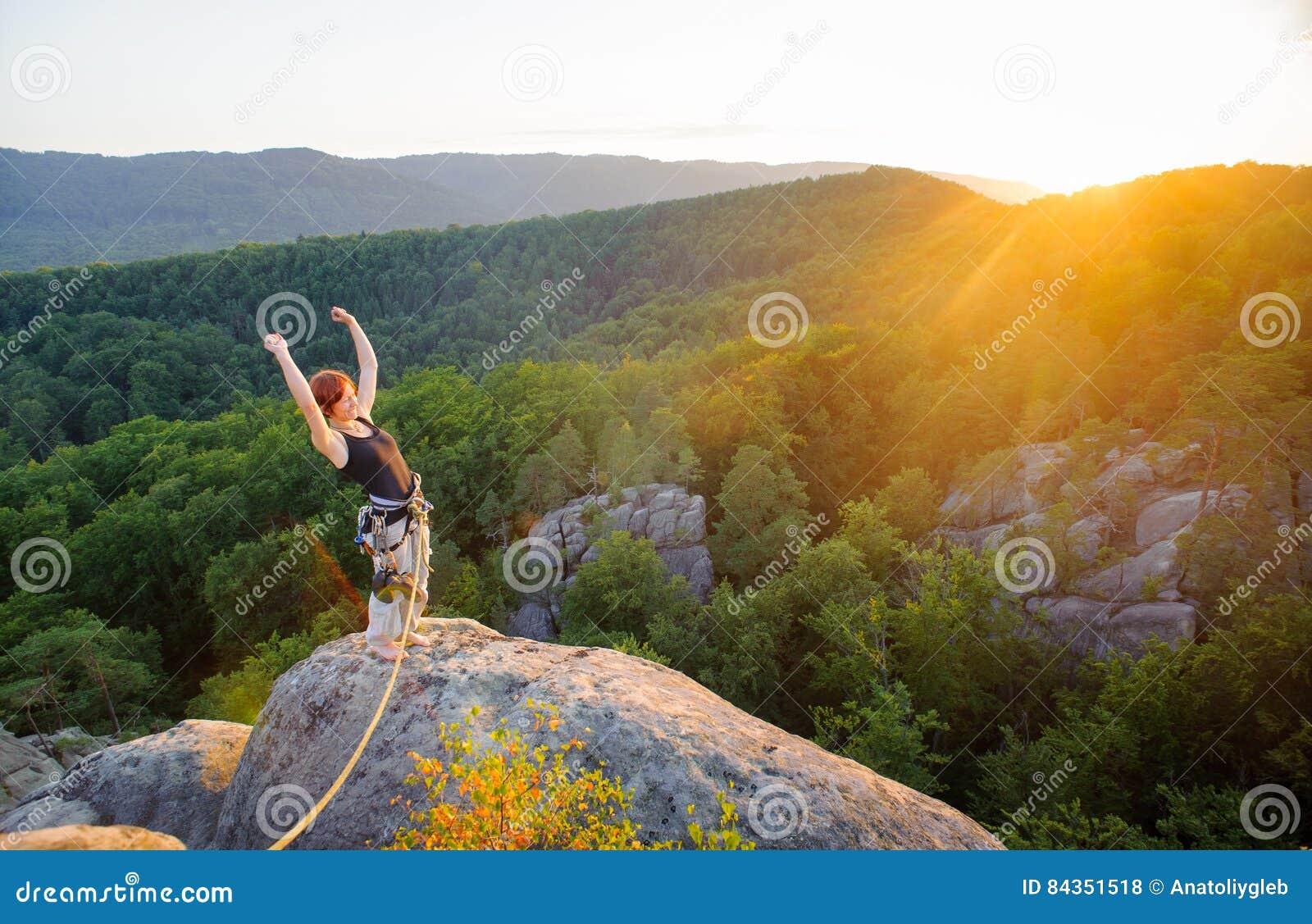 Flickaklättrare på bergmaximum på hög höjd i afton