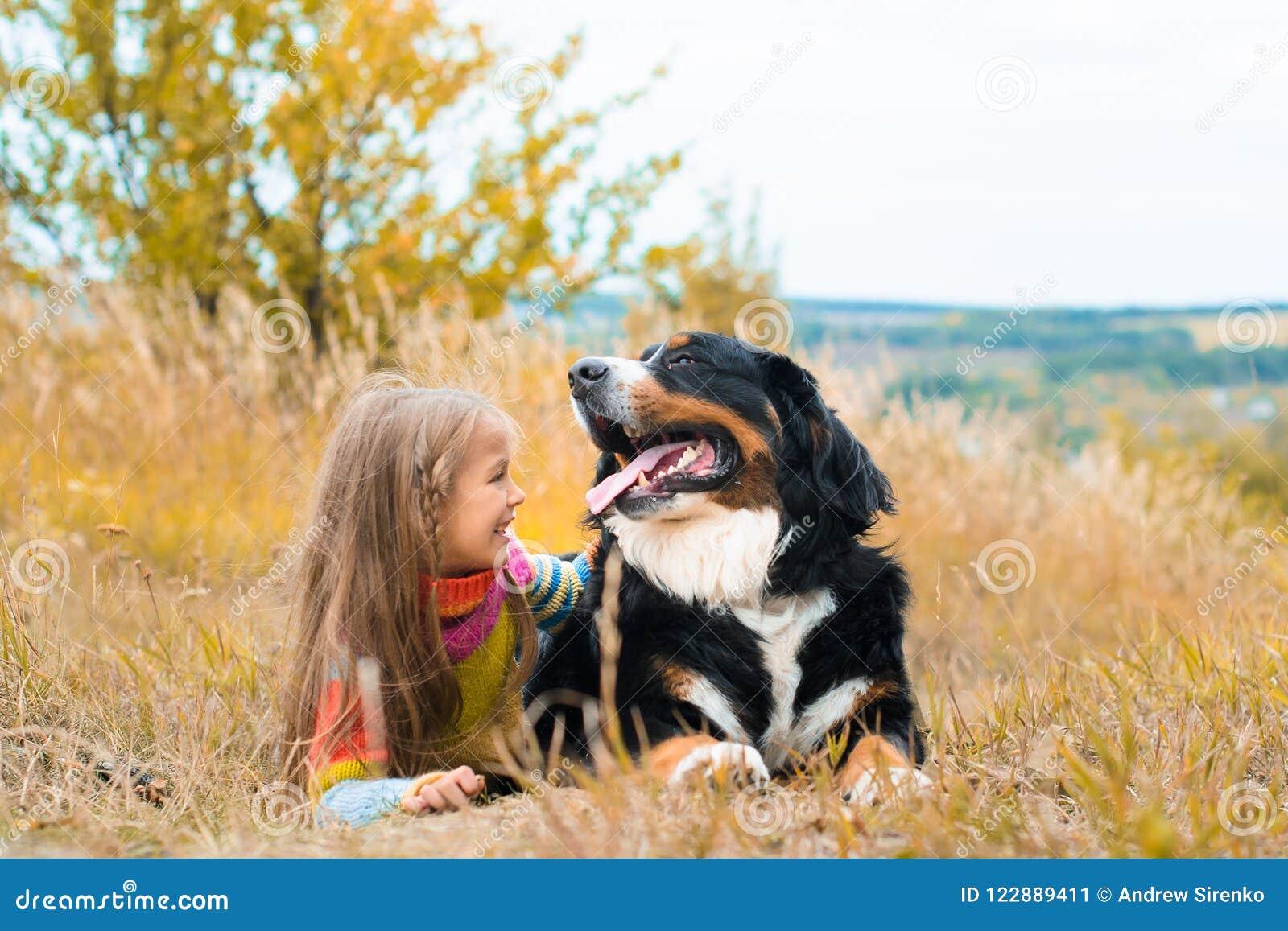 Flickalögner bredvid stor hund på höst går