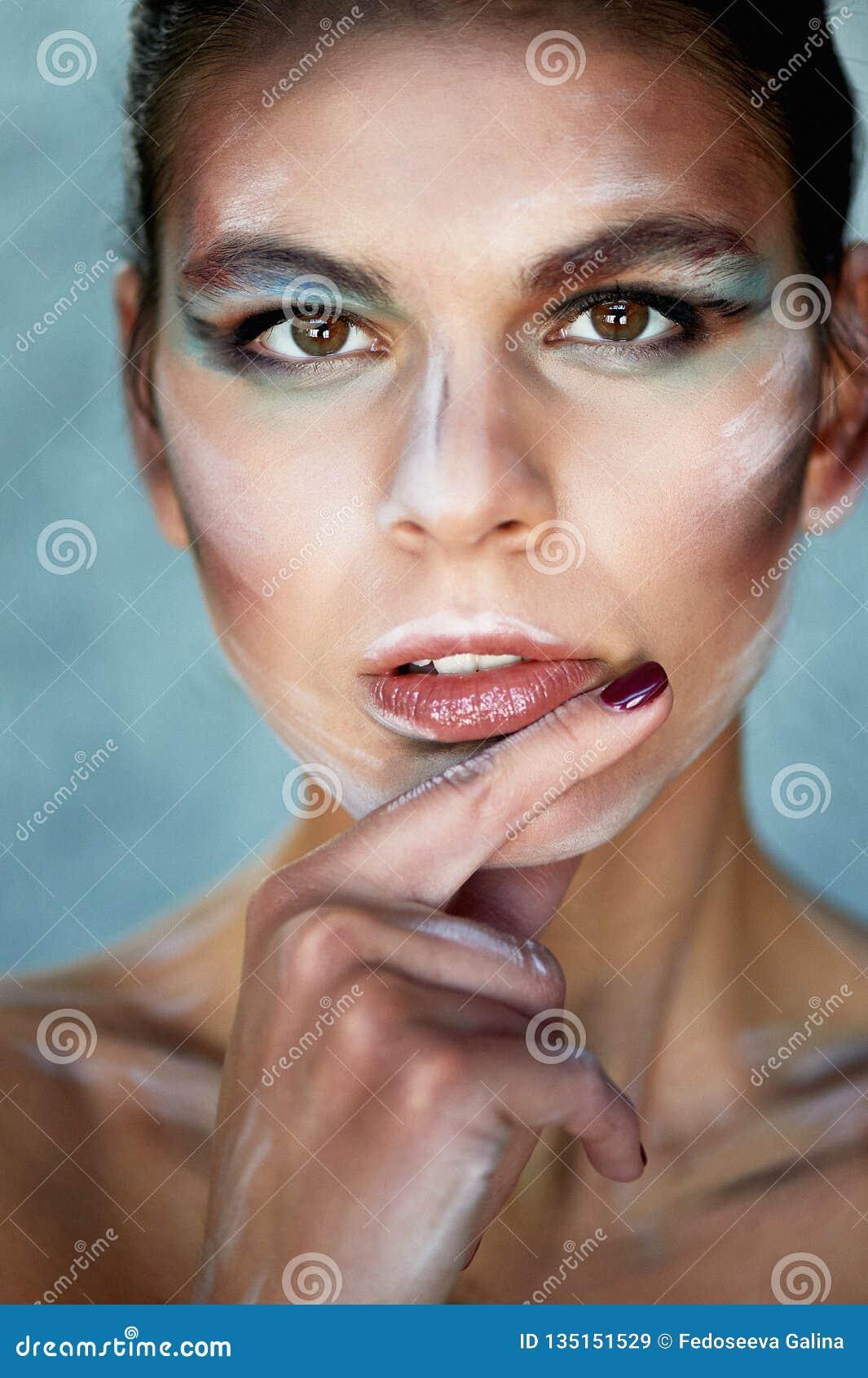 Flickamodell med idérik makeup, målarfärgslaglängder på framsidan idérik person Finger i munnen Se eftertänksam
