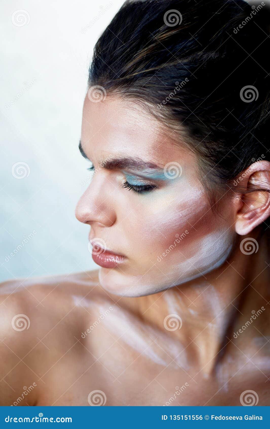 Flickamodell med idérik makeup, målarfärgslaglängder på framsidan idérik person Se till sidan Lyftt skuldra