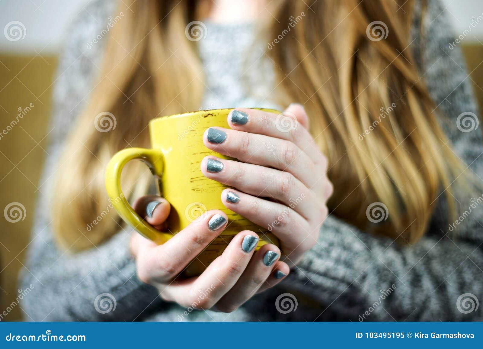 Flickan är den hållande koppen kaffe eller te i händer med grå färgsilvermanikyr