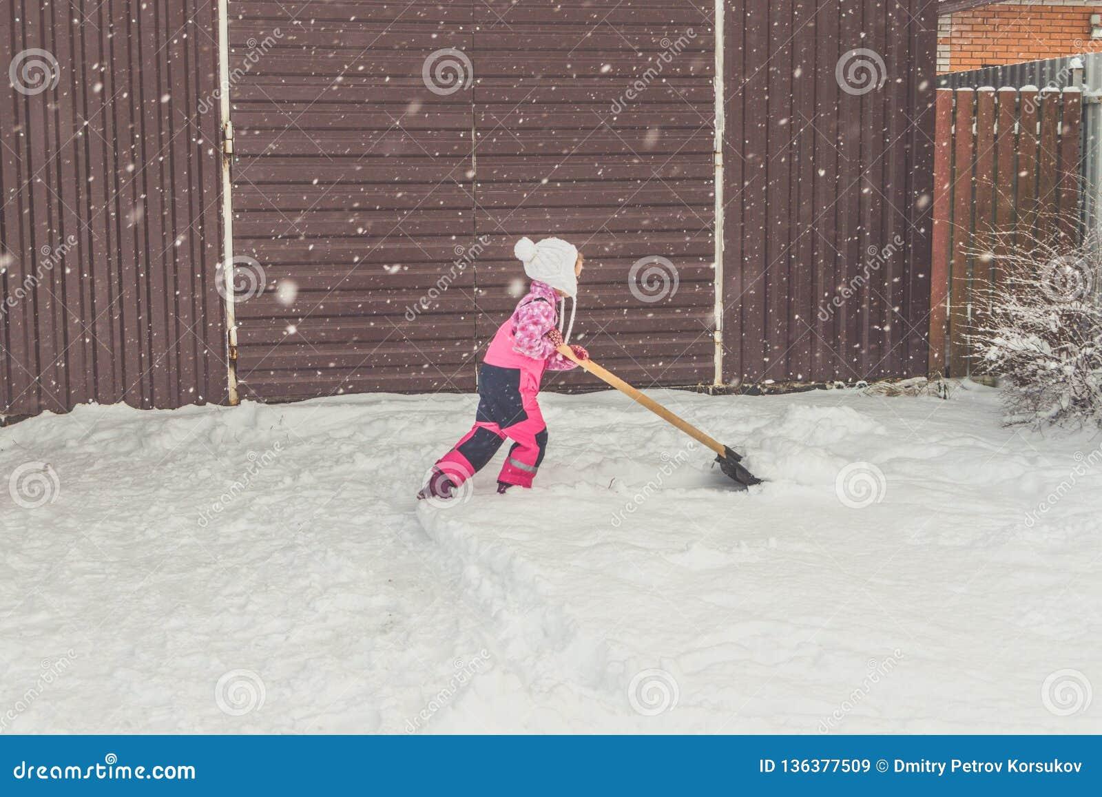 Flickan behandla som ett barn den stora skyffeln tar bort snö från banan i trädgården på garaget