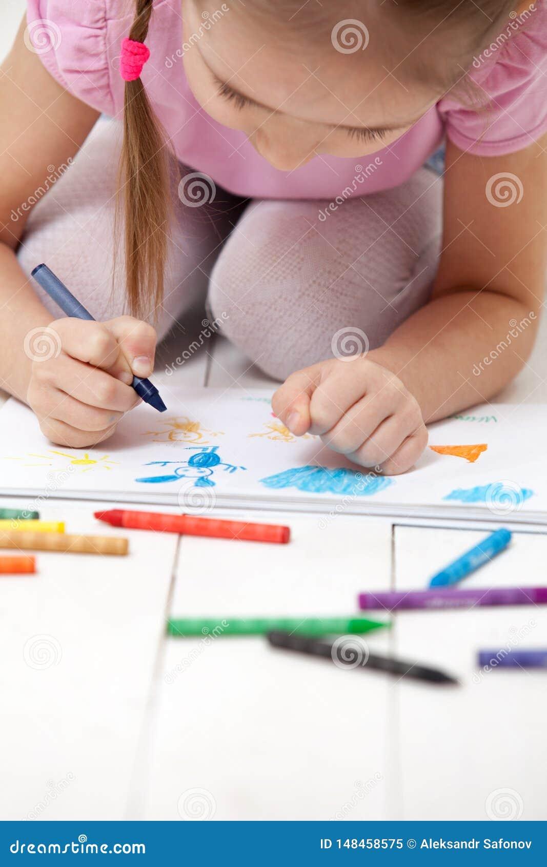 Flickan drar med färgpennor i albumet