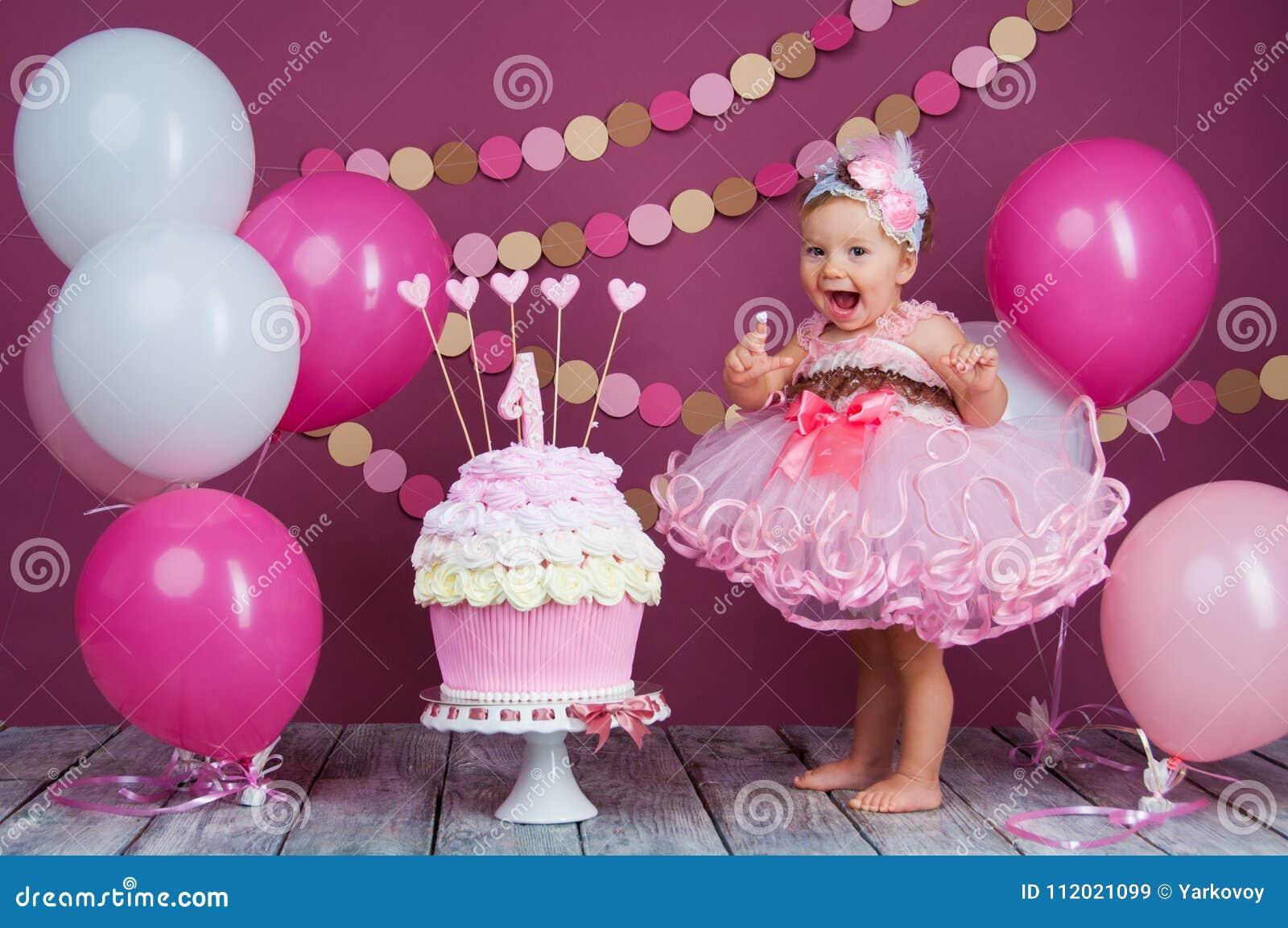 Flickan för födelsedagen för liten flicka` s suddades in i en kaka Den första kakan Bruket av den första kakan Dundersuccékaka