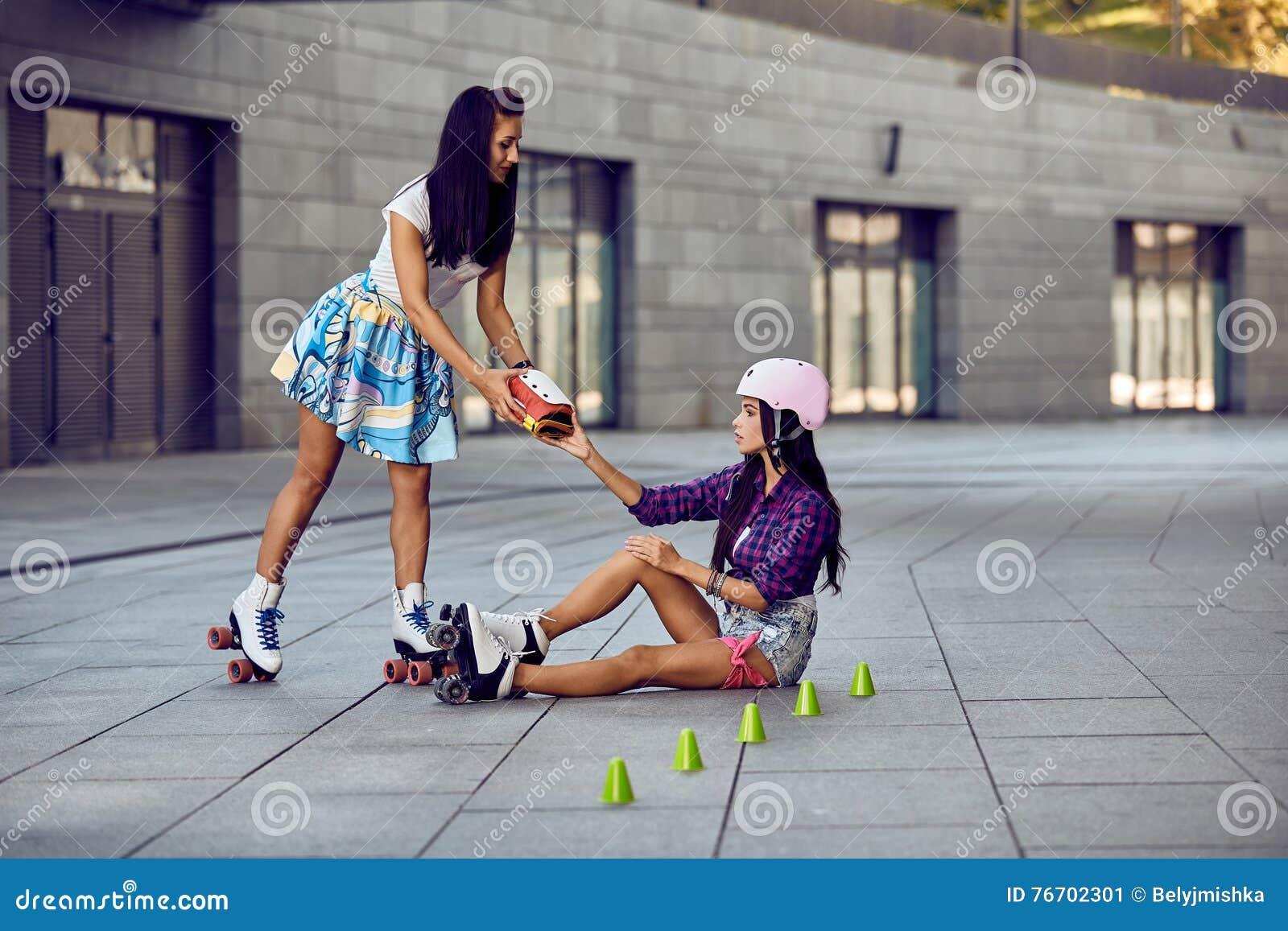 Flickan faller ner och skrapar benet, når han har rollerblading