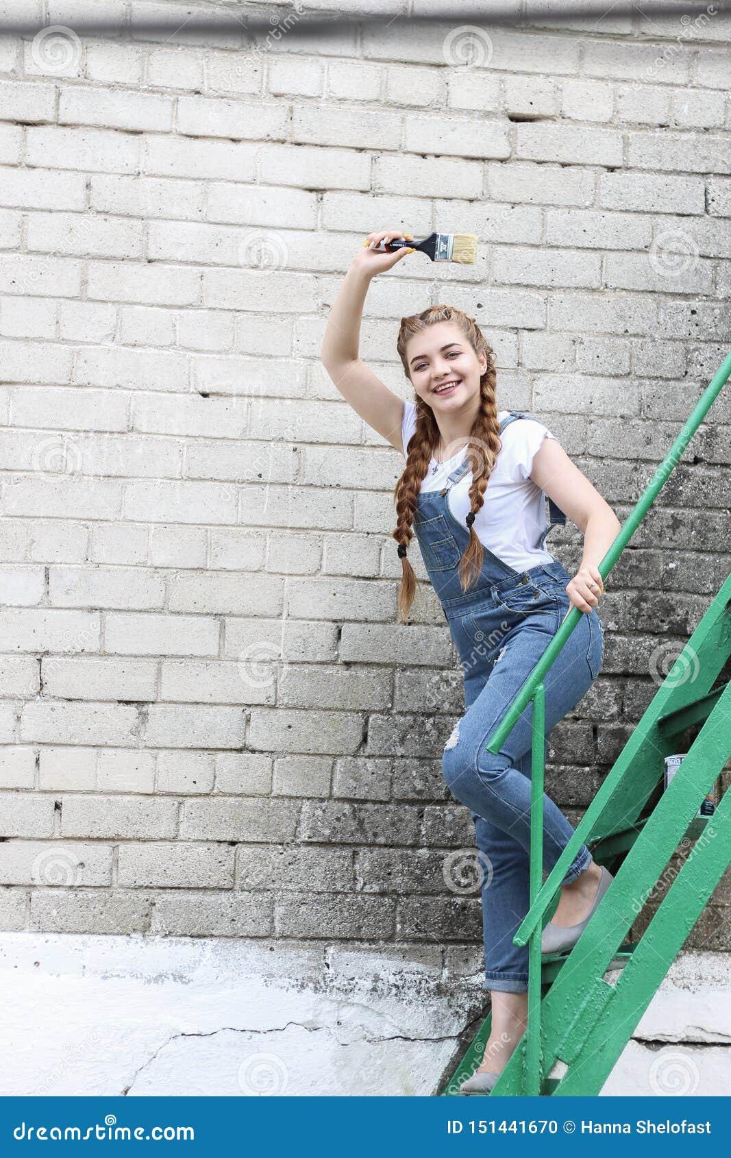 Flickan gör att förbereda sig för att måla en träyttersidagazebo, staket