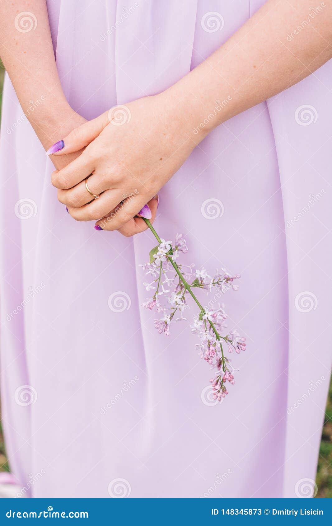 Flickan g?mma i handflatan i delikat f?rg med en bukett av blommor