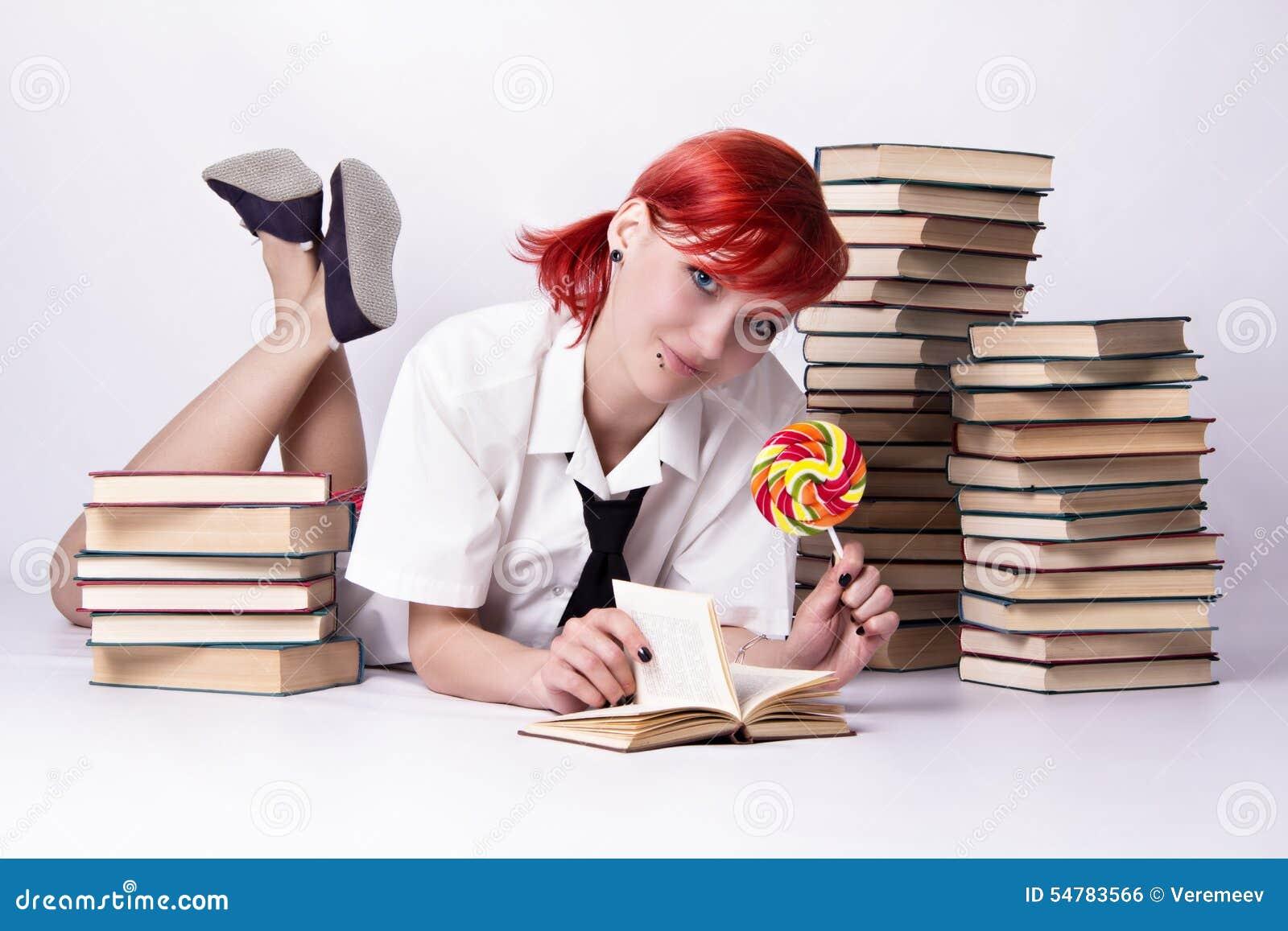 Flickan i animestil med godisen och böcker