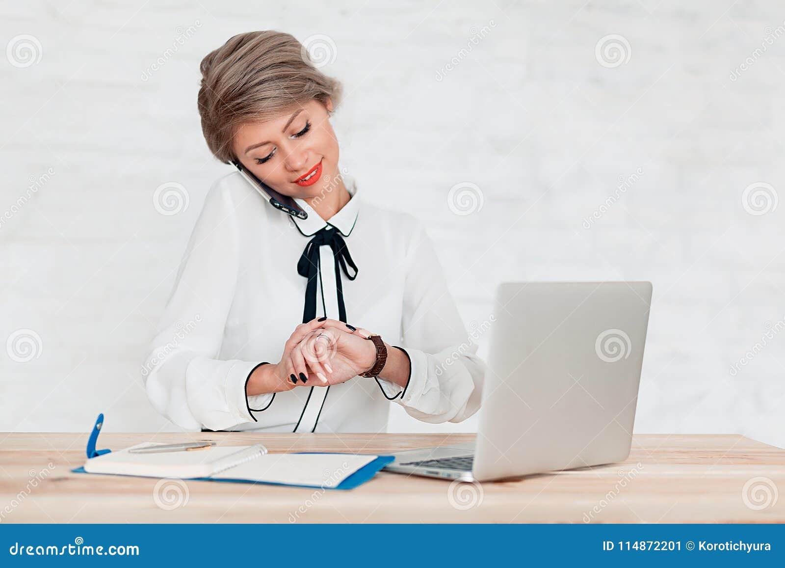 Flickan i den vita blusen sitter på tabellen med bärbara datorn och ser klockan