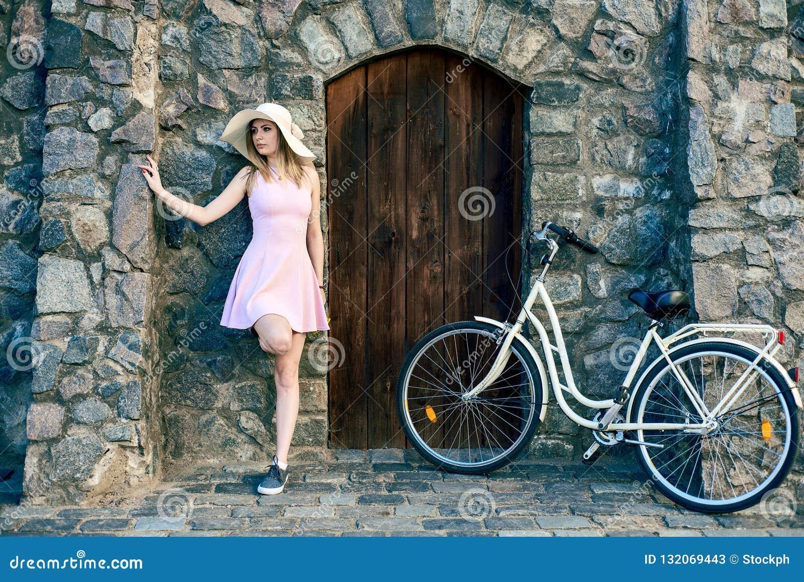 Flickan i en rosa klänning och en sugrörhatt står bredvid en texturerad sten, gammal vägg med en trädörr
