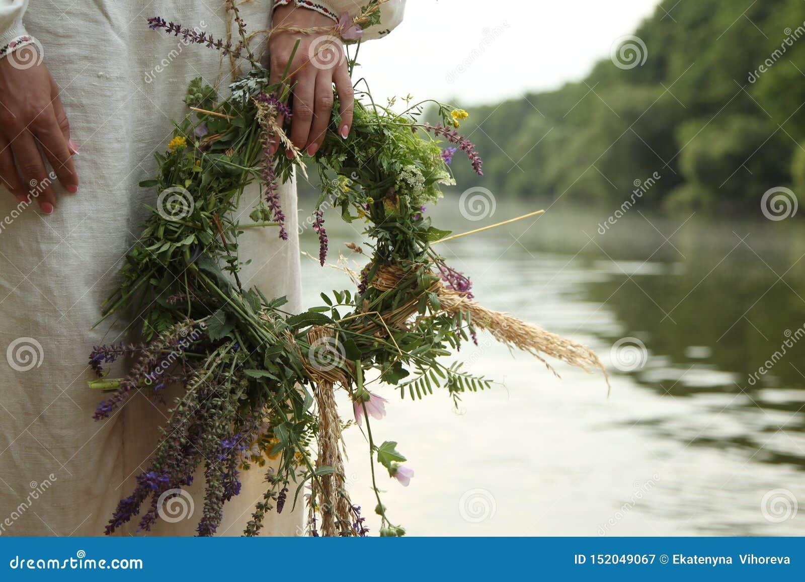 Flickan i slavisk kläder med en krans på bakgrunden av floden