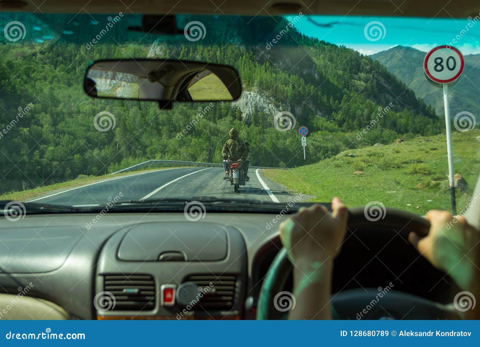 Flickan kör längs asfaltvägen i den Altai bergalen