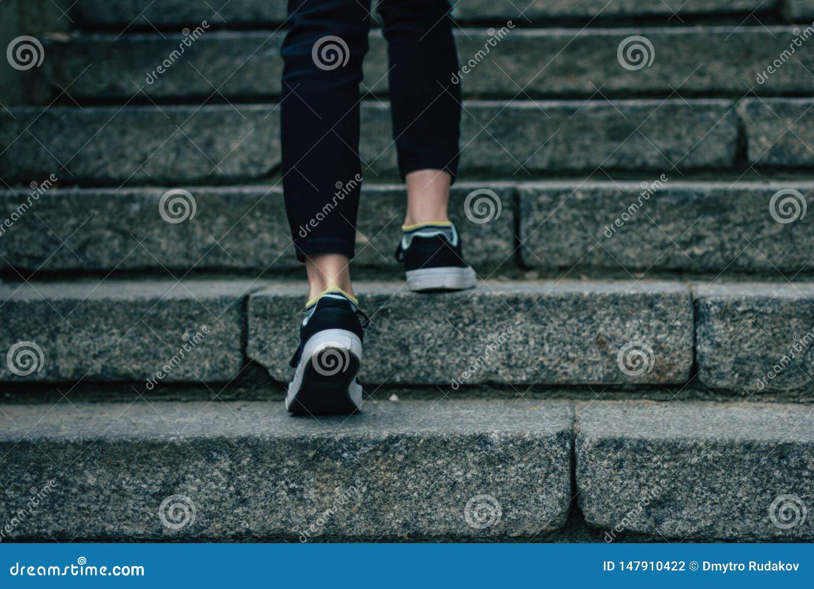 Flickan klättrar på konkret trappa