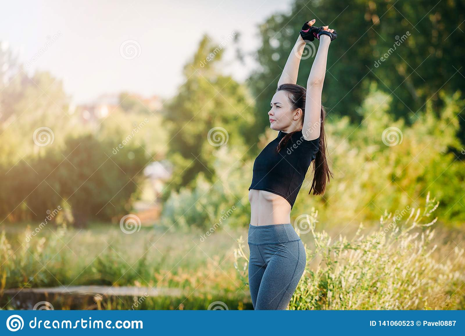 Flickan kopplas in i gymnastik i stad parkerar Kondition i natur Morgonövning med en härlig idrotts- kvinna