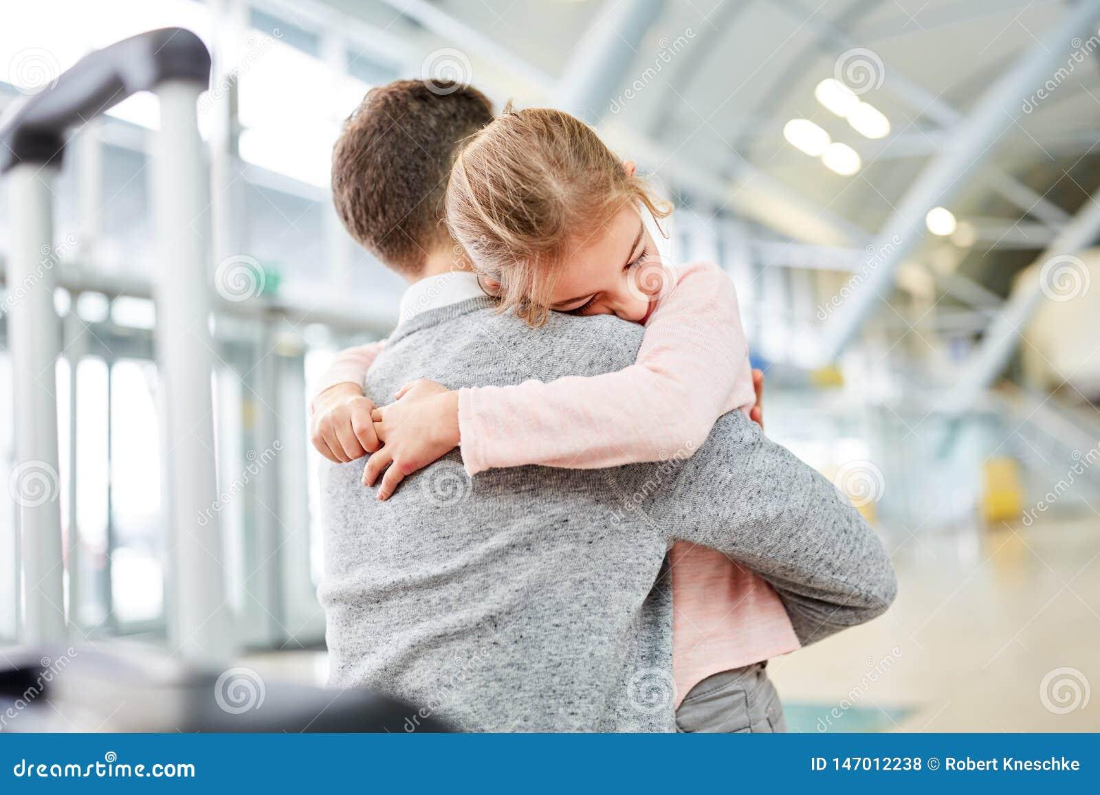 Flickan kramar hennes fader i flygplatsterminalen