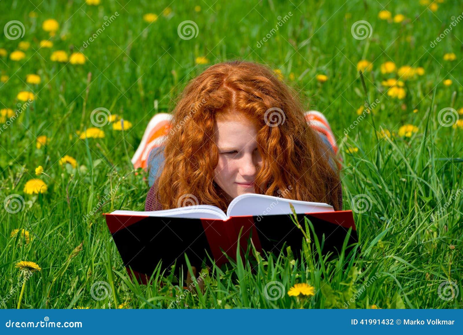 Flickan läser i våräng