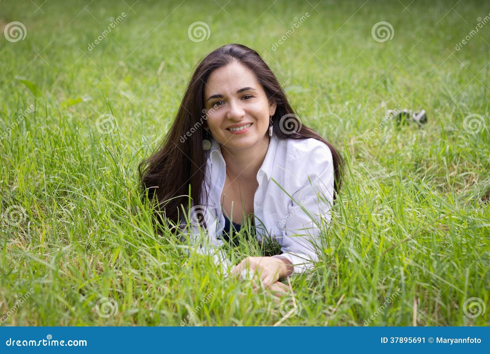 Flickan ligger i ett grönt gräs