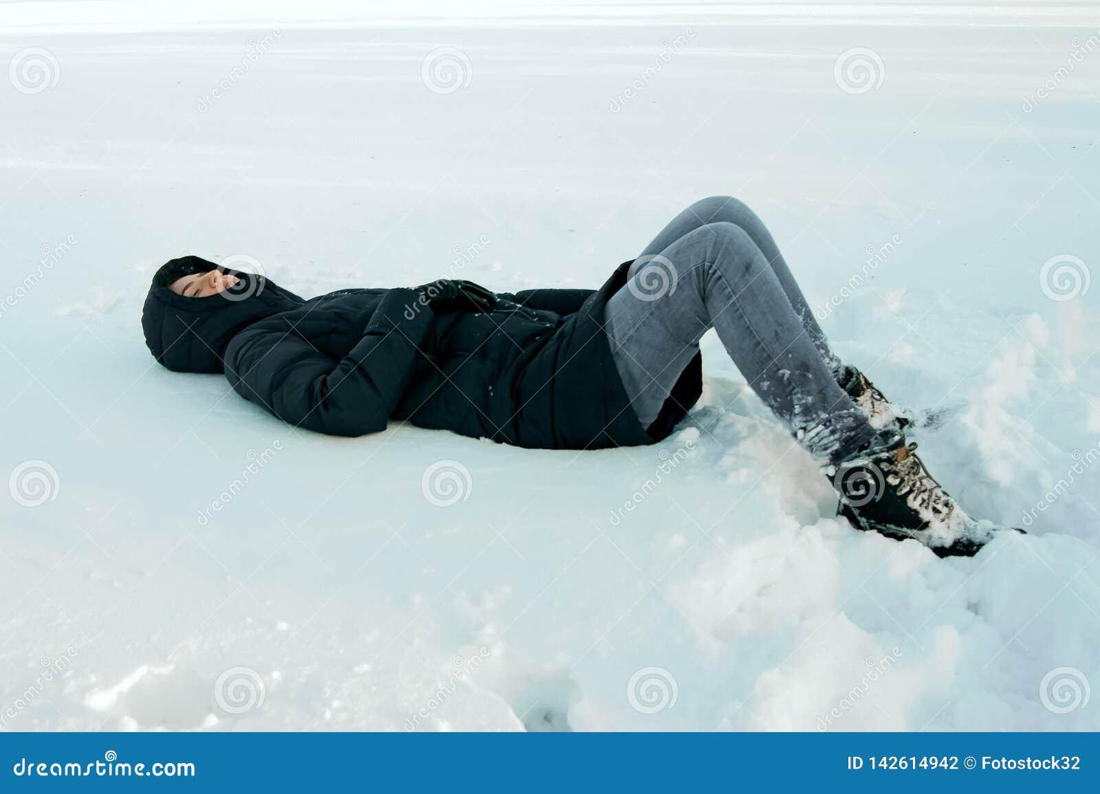 Flickan ligger i snön