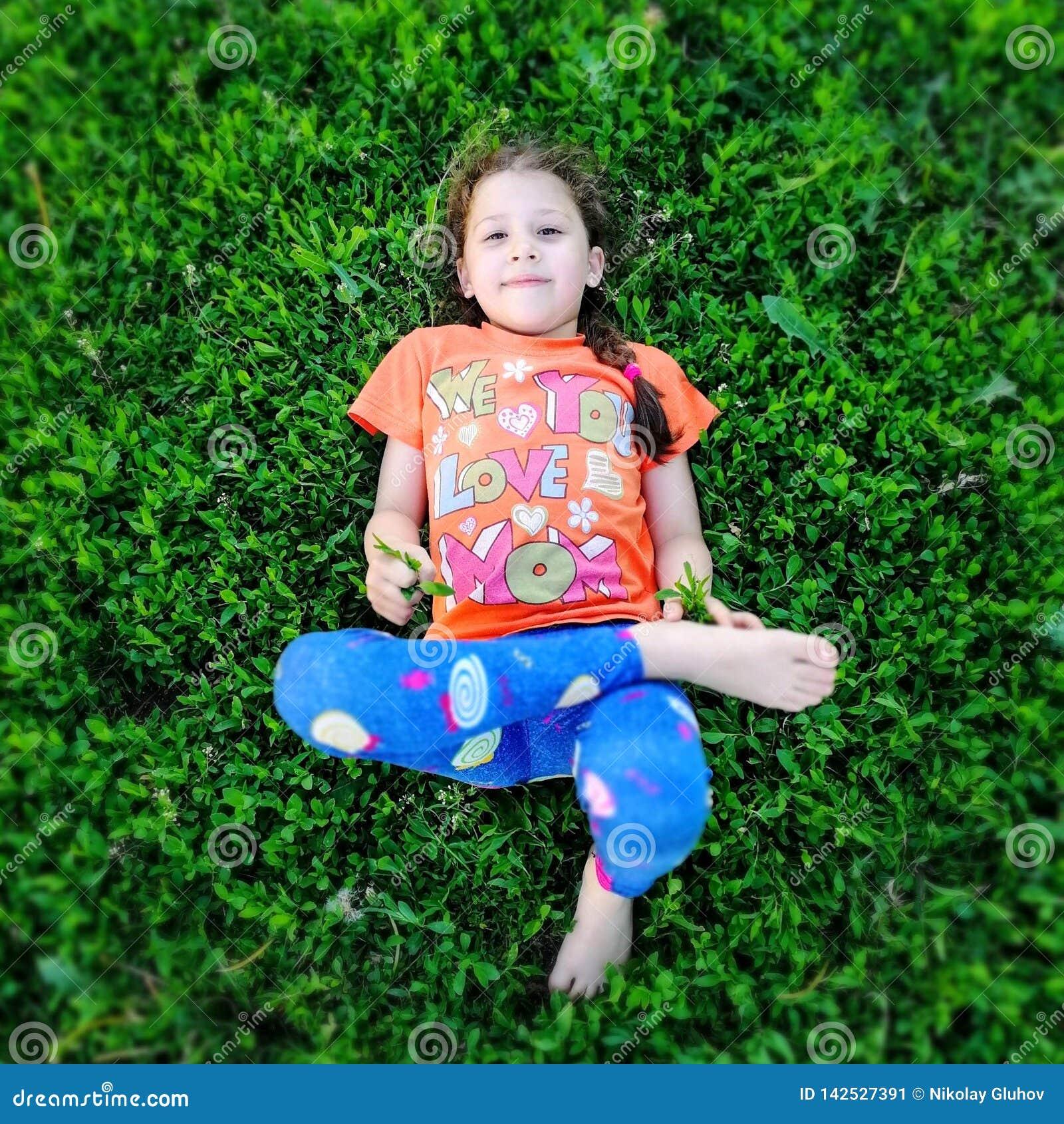 Flickan ligger på det gröna gräset och ser upp