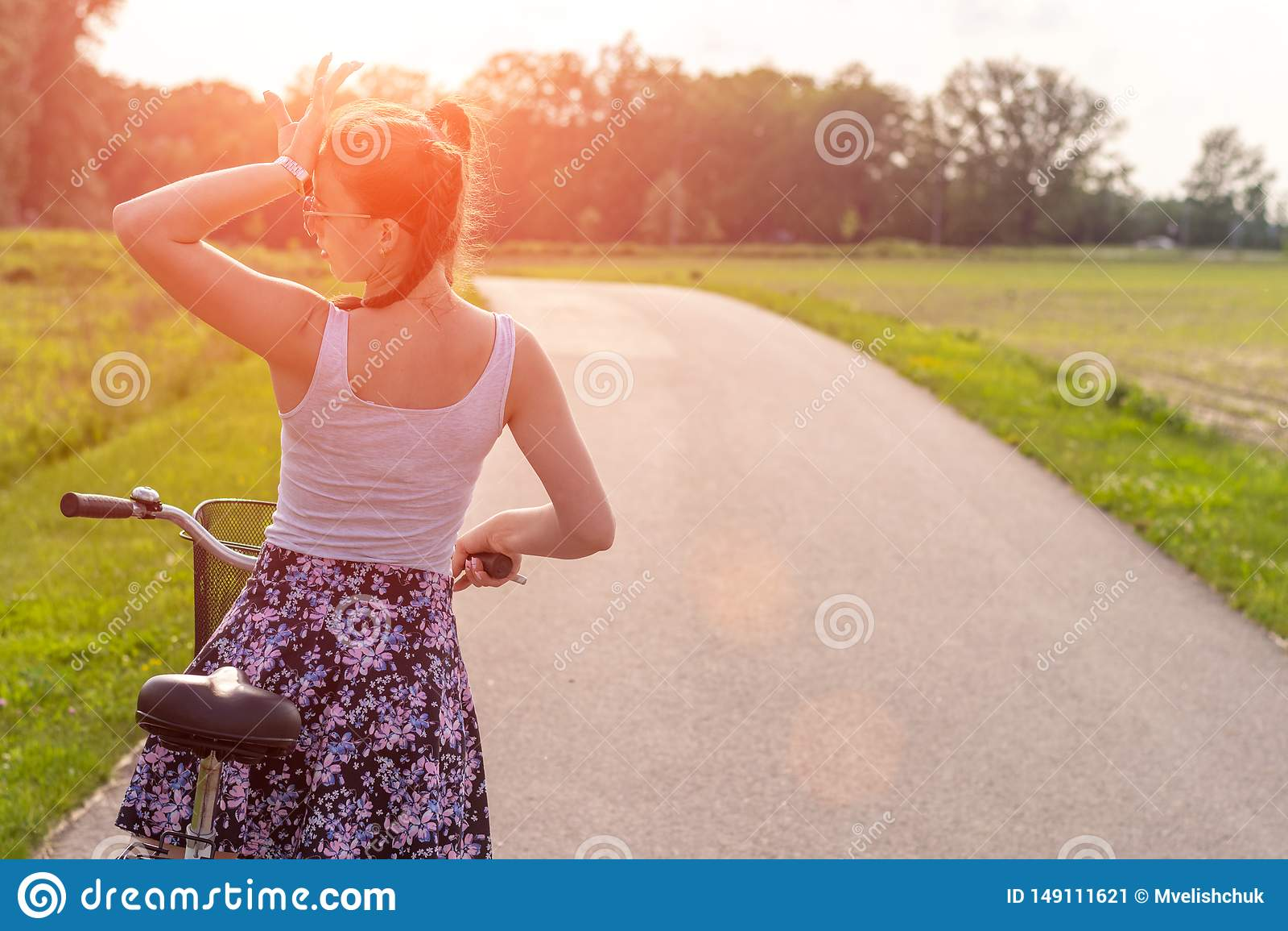 Flickan med cykeln p? sommarsolnedg?ngen p? v?gen i staden parkerar Cirkuleringscloseuphjul p? suddig sommarbakgrund Cykla ner t